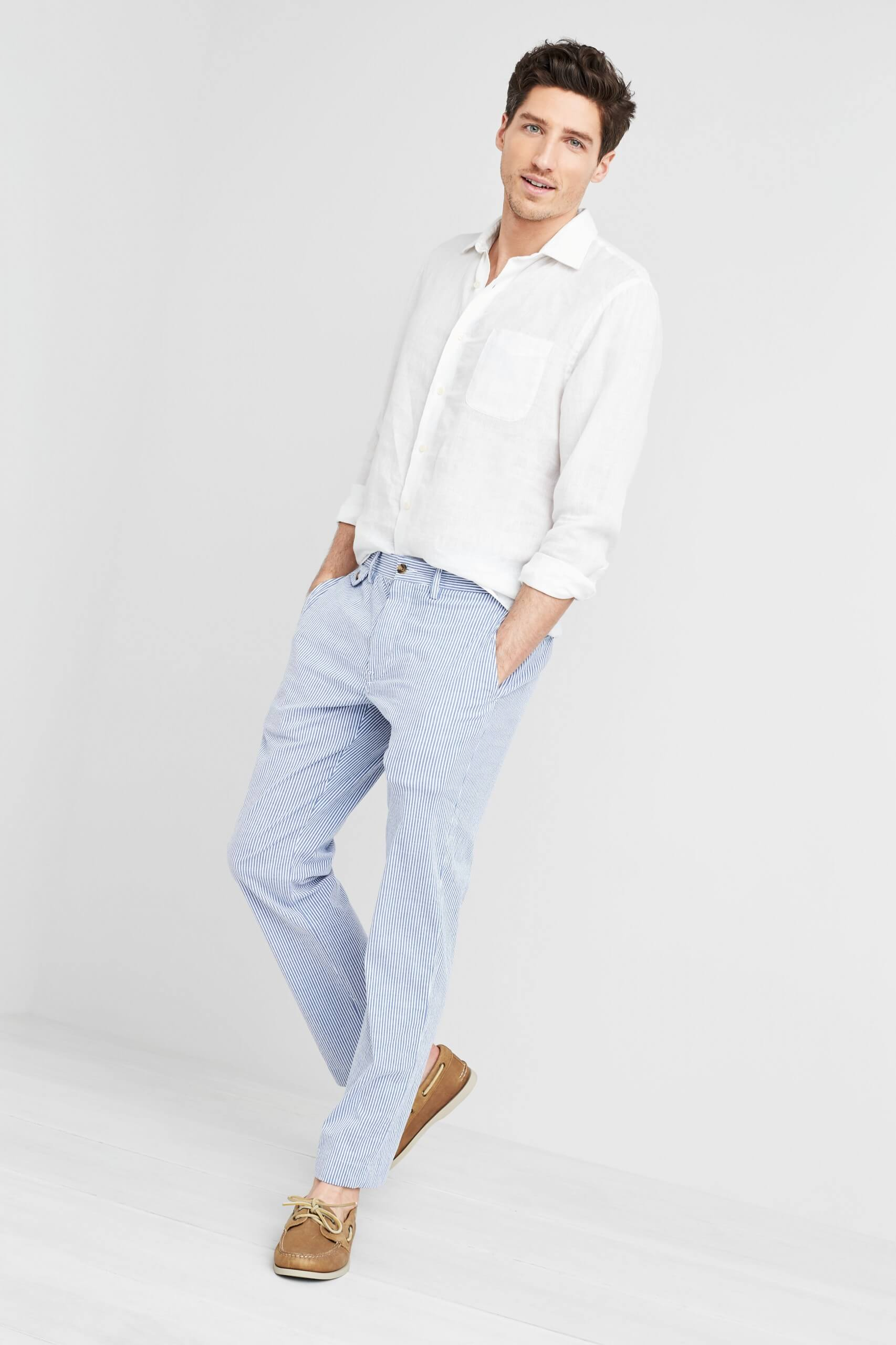 Stitch Fix Men's model wearing white button-down shirt, blue chinos and brown boat shoes.