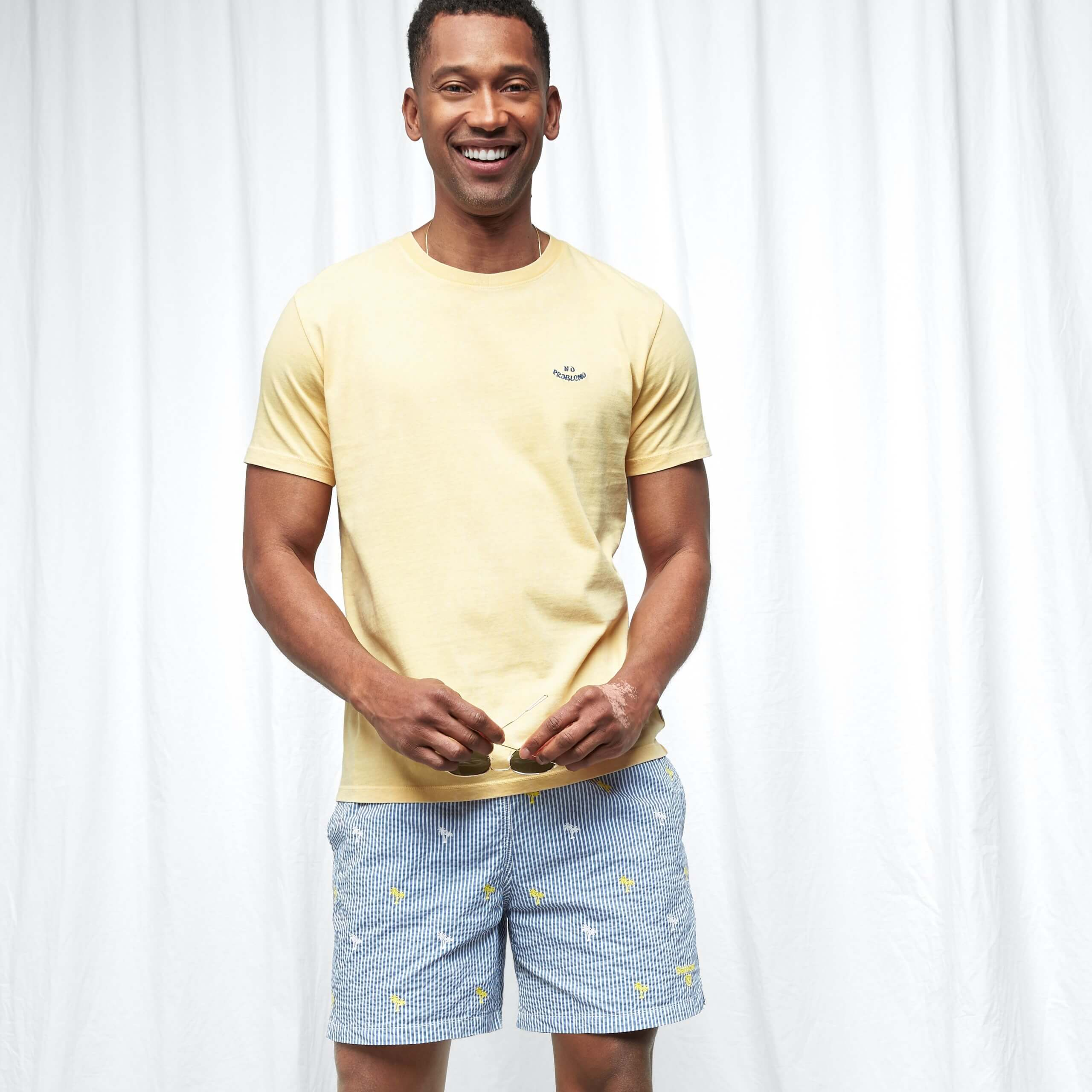 Stitch Fix Men's model wearing yellow t-shirt and blue shorts with palm tree details.