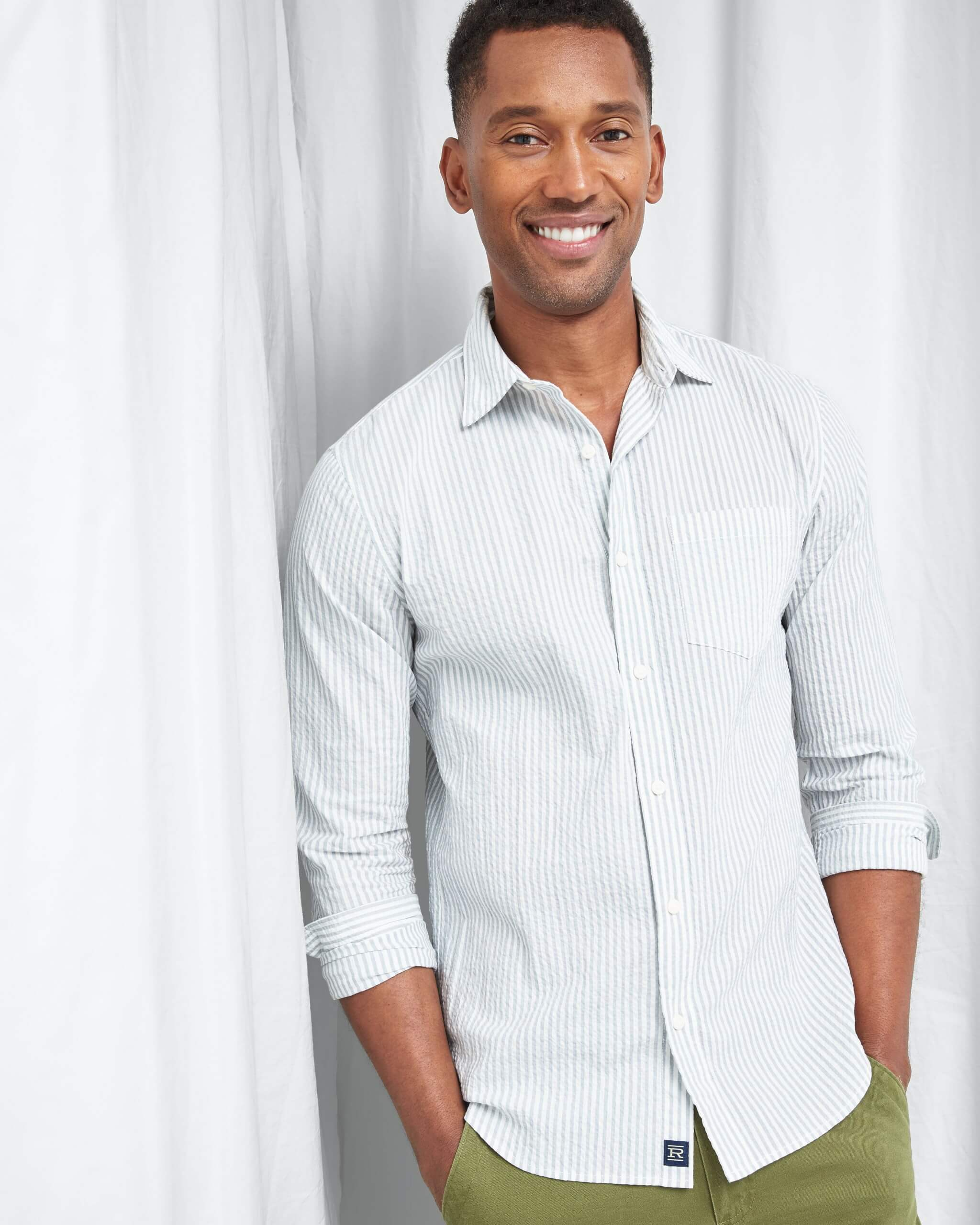 Stitch Fix Men's model standing wearing white and light blue striped button-down shirt and green pants.