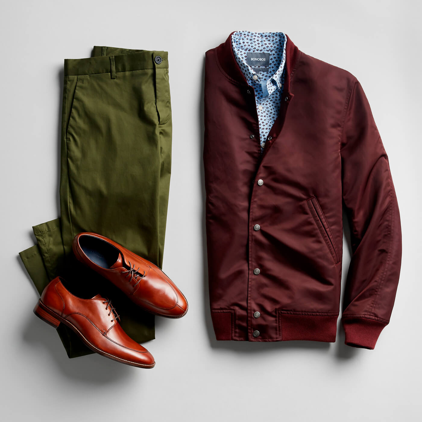 blue floral print shirt, maroon bomber jacket, cognac dress shoes and green chinos
