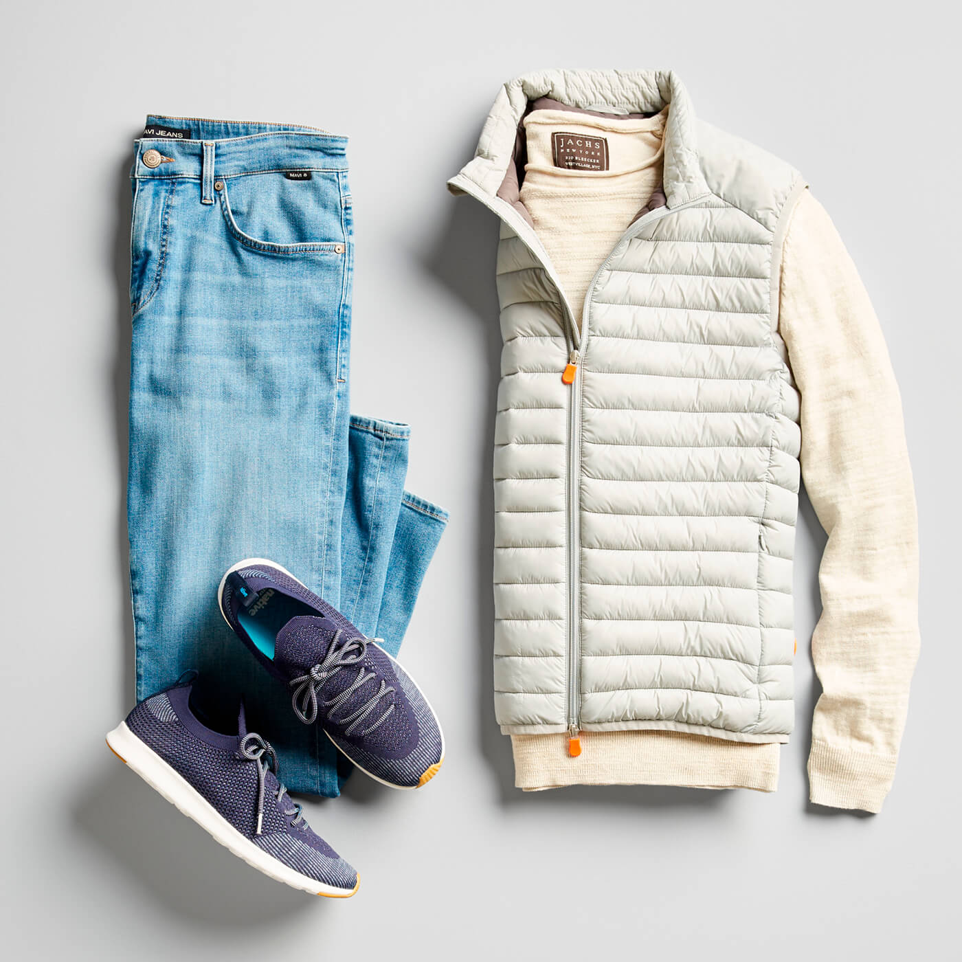 light wash jeans, blue sneakers, and light tan puffer vest