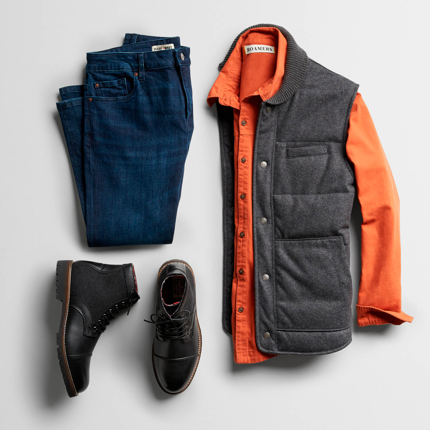 orange flannel shirt, grey vest, navy chinos and black chukka boots