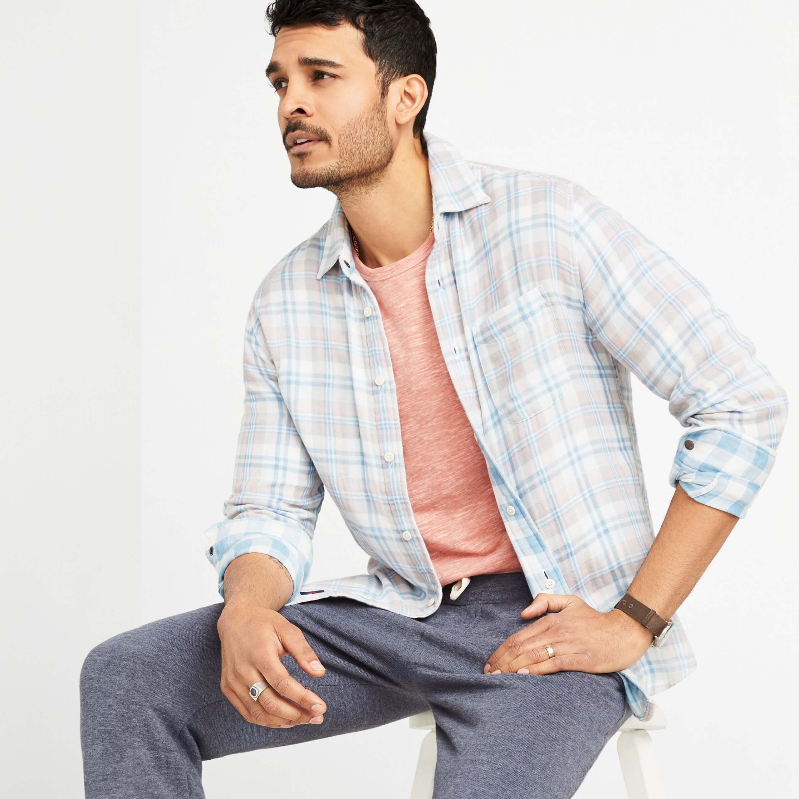 Stitch Fix Men's model sitting on a white stool wearing pink terry crew sweatshirt under a plaid button-down shirt with fleece pants sitting on white stool.