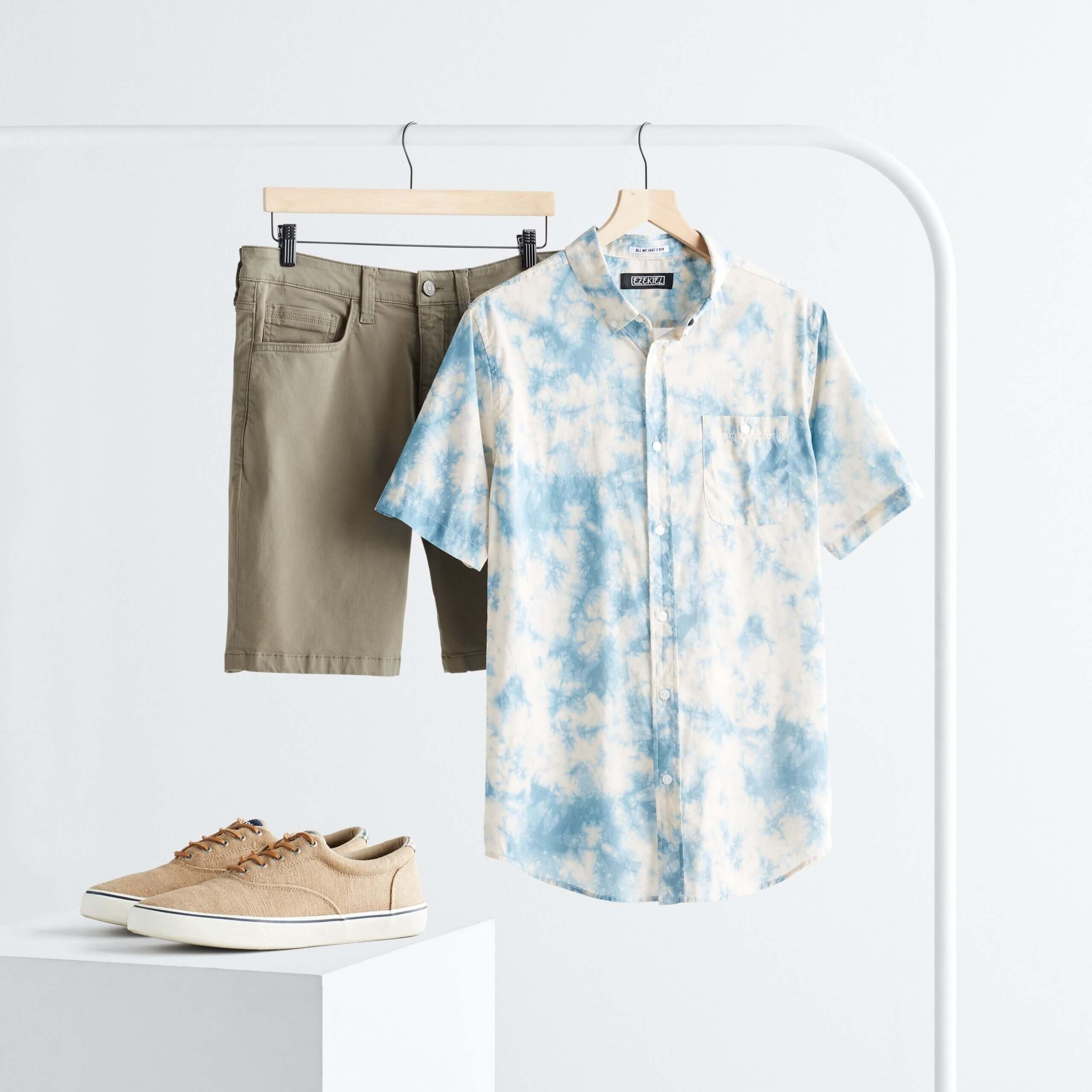 Stitch Fix men's rack image with blue tie-dye button-down short sleeve shirt and olive shorts hanging on white rack next to tan leather sneakers on white block.