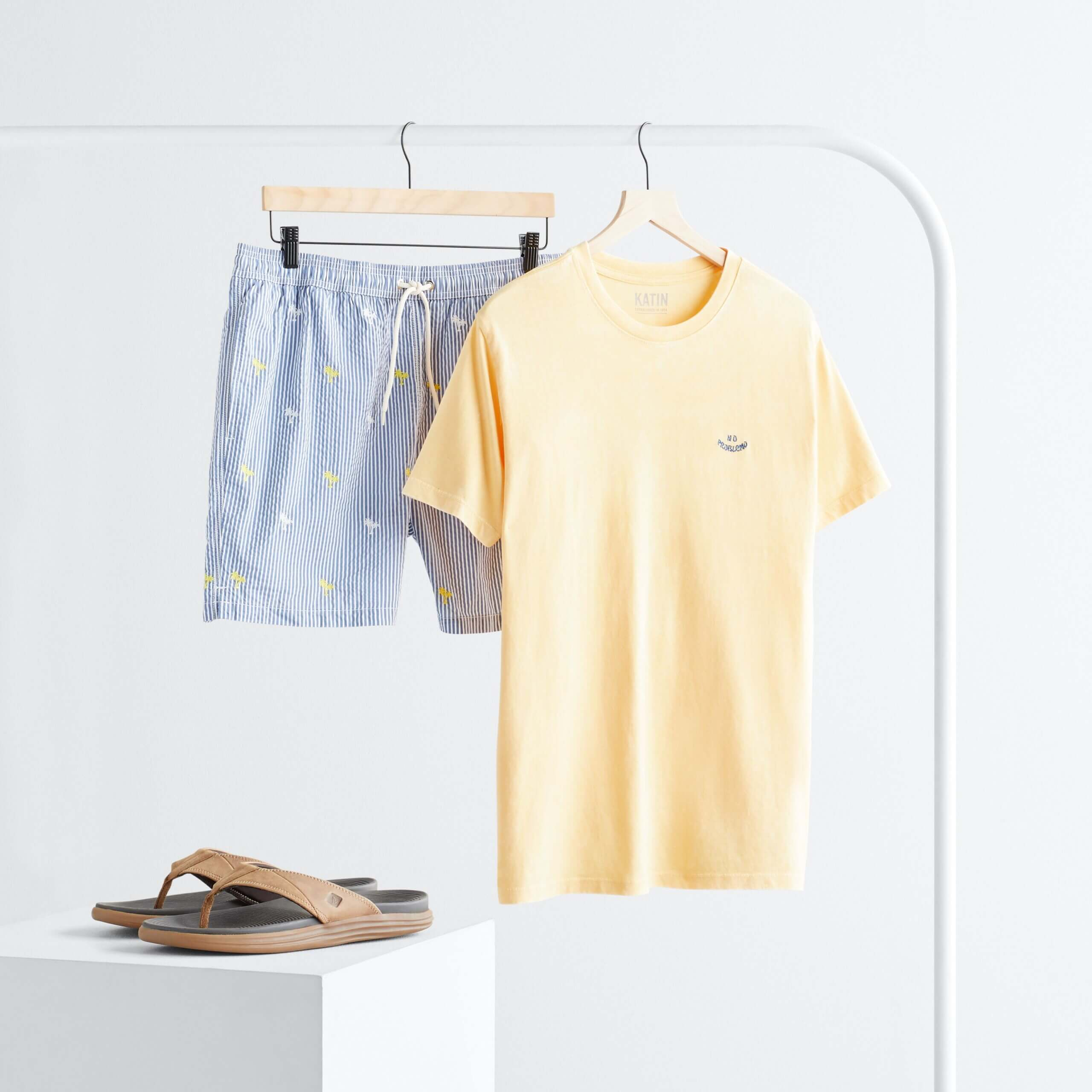 Stitch Fix Men's rack image with yellow short sleeve graphic tee and blue striped shorts hanging on white rack next to brown flip flops on white block.
