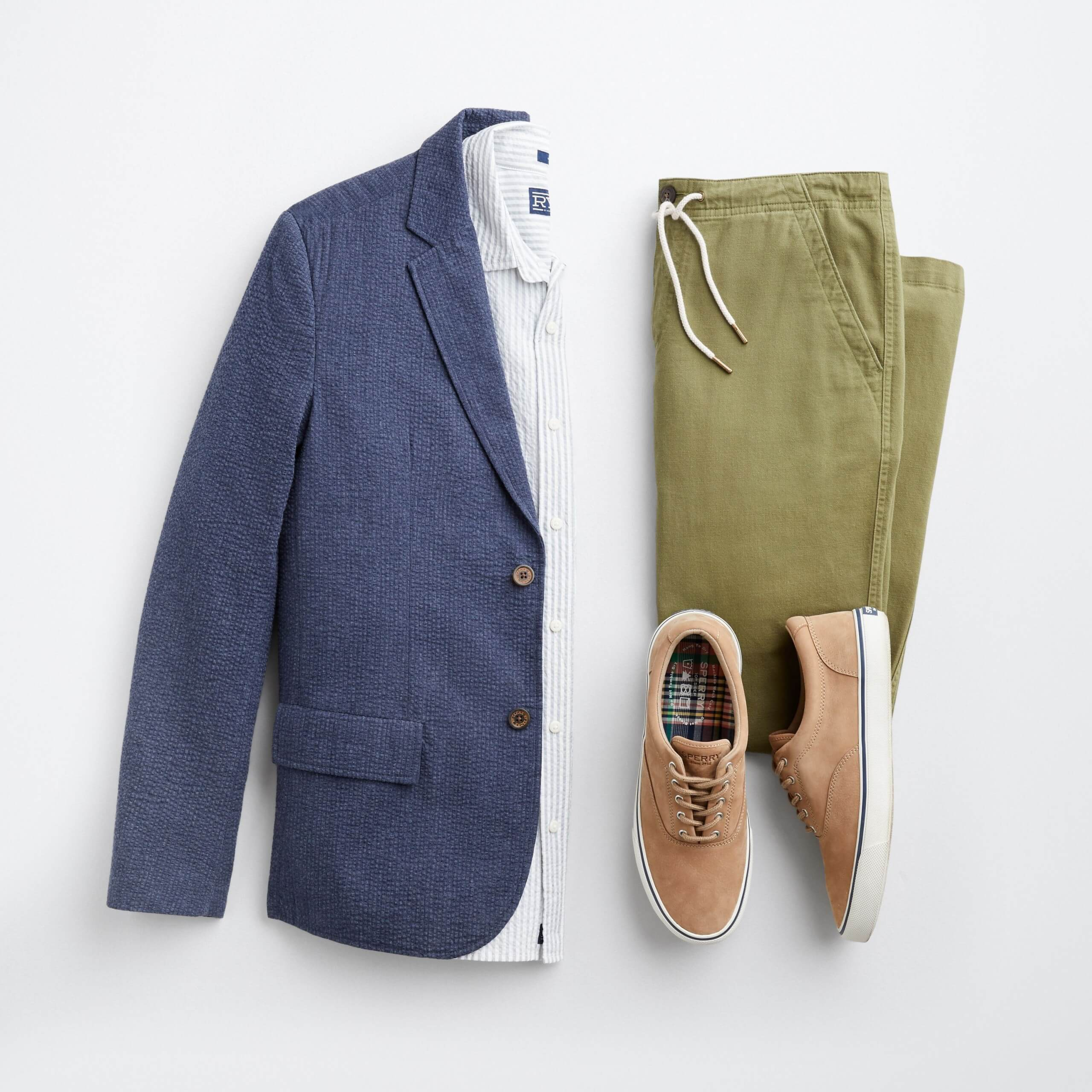 Stitch Fix Men's outfit laydown featuring navy blazer over white and blue striped button-down dress shirt, olive green pants and tan leather sneakers.