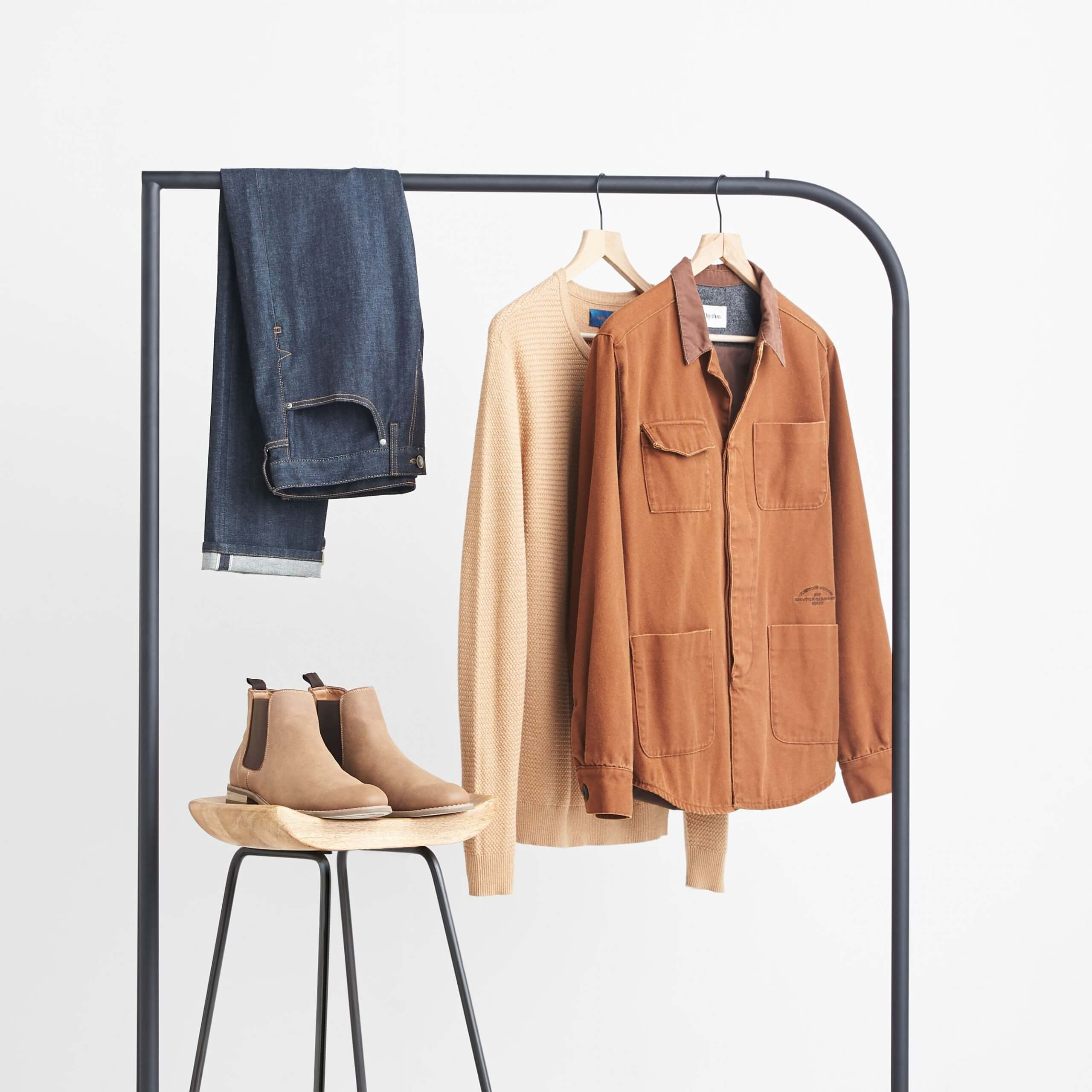 Stitch Fix Men's brown chore jacket, tan crewneck sweater and slim-fit dark wash jeans hanging on a black rack next to brown boots sitting on a wooden stool.