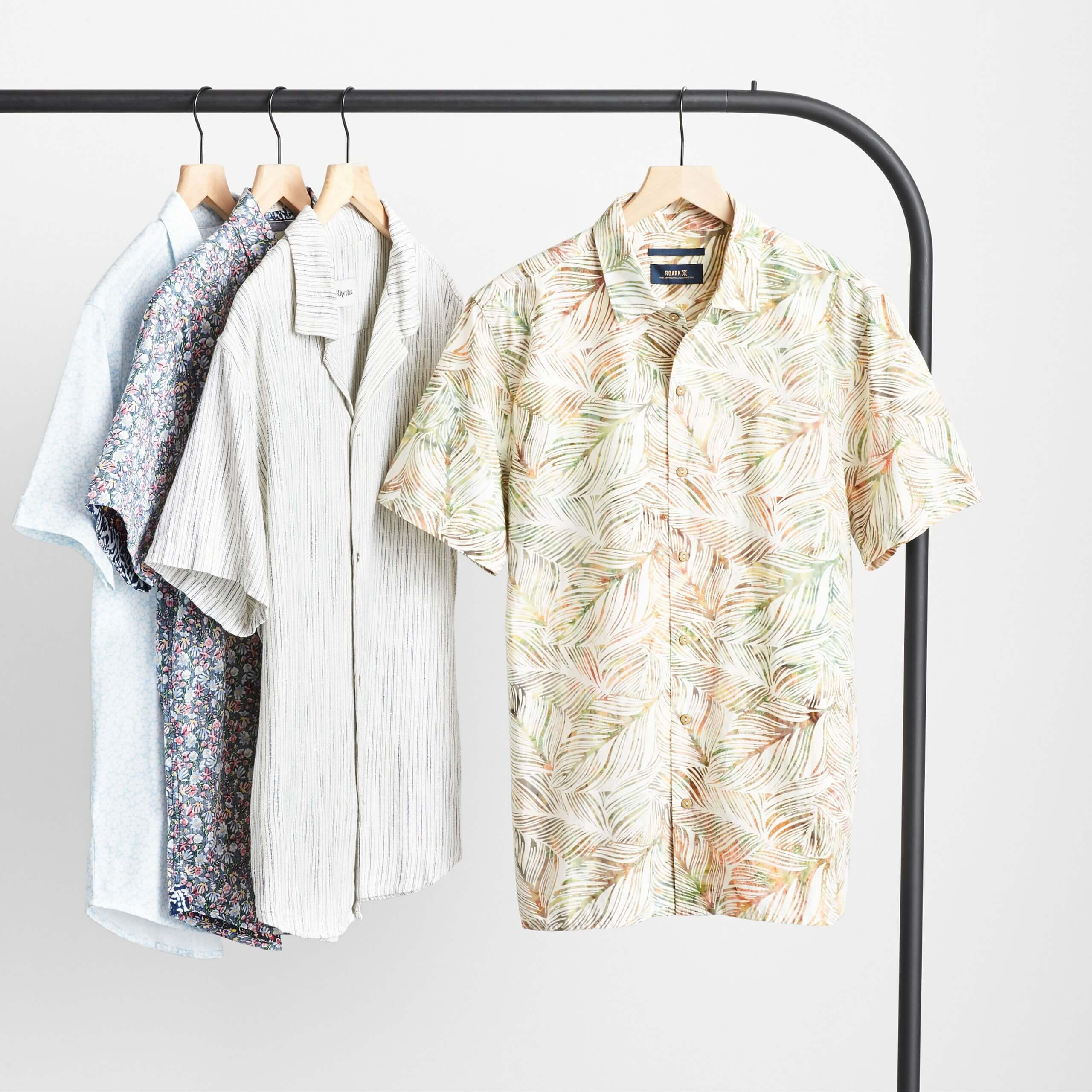Stitch Fix Men's four patterned short-sleeved button-downs hanging on a black rack.