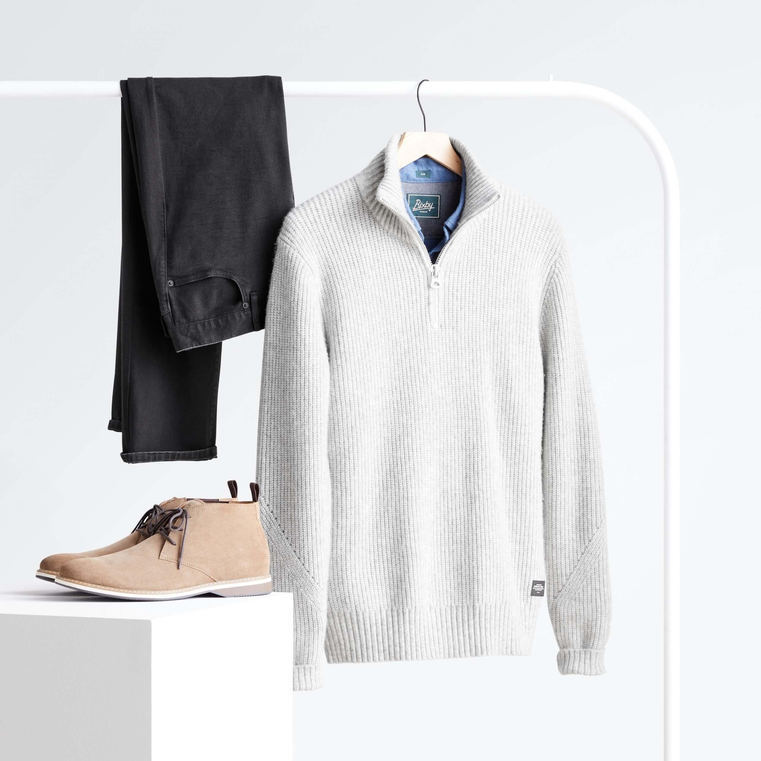 Stitch Fix Men's light grey quarter zip sweater over blue button-down, black jeans hanging on white rack next to beige chukkas on white podium.
