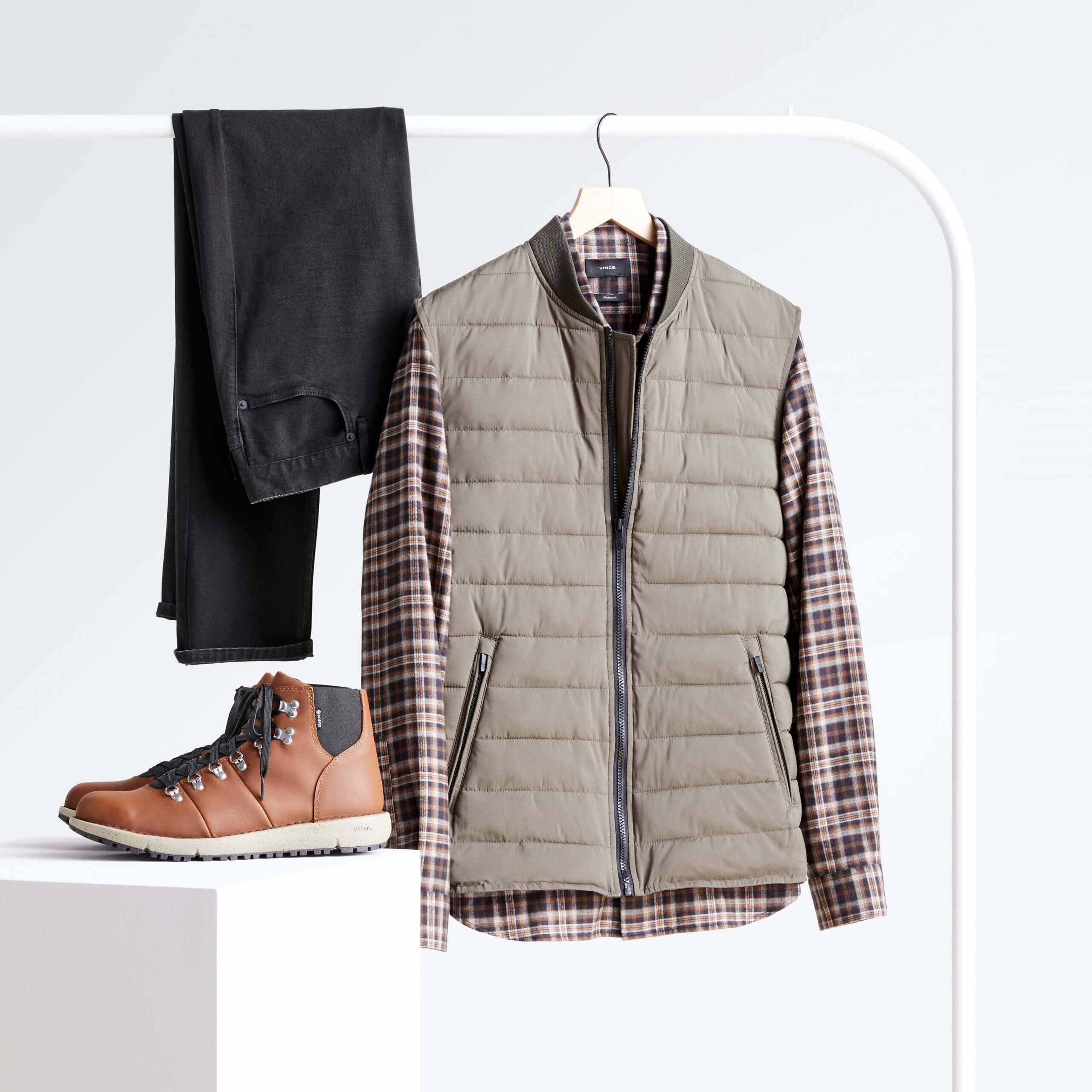 Stitch Fix Men's grey vest over plaid shirt and black jeans hanging on white rack, next to brown hiker boots on white block.