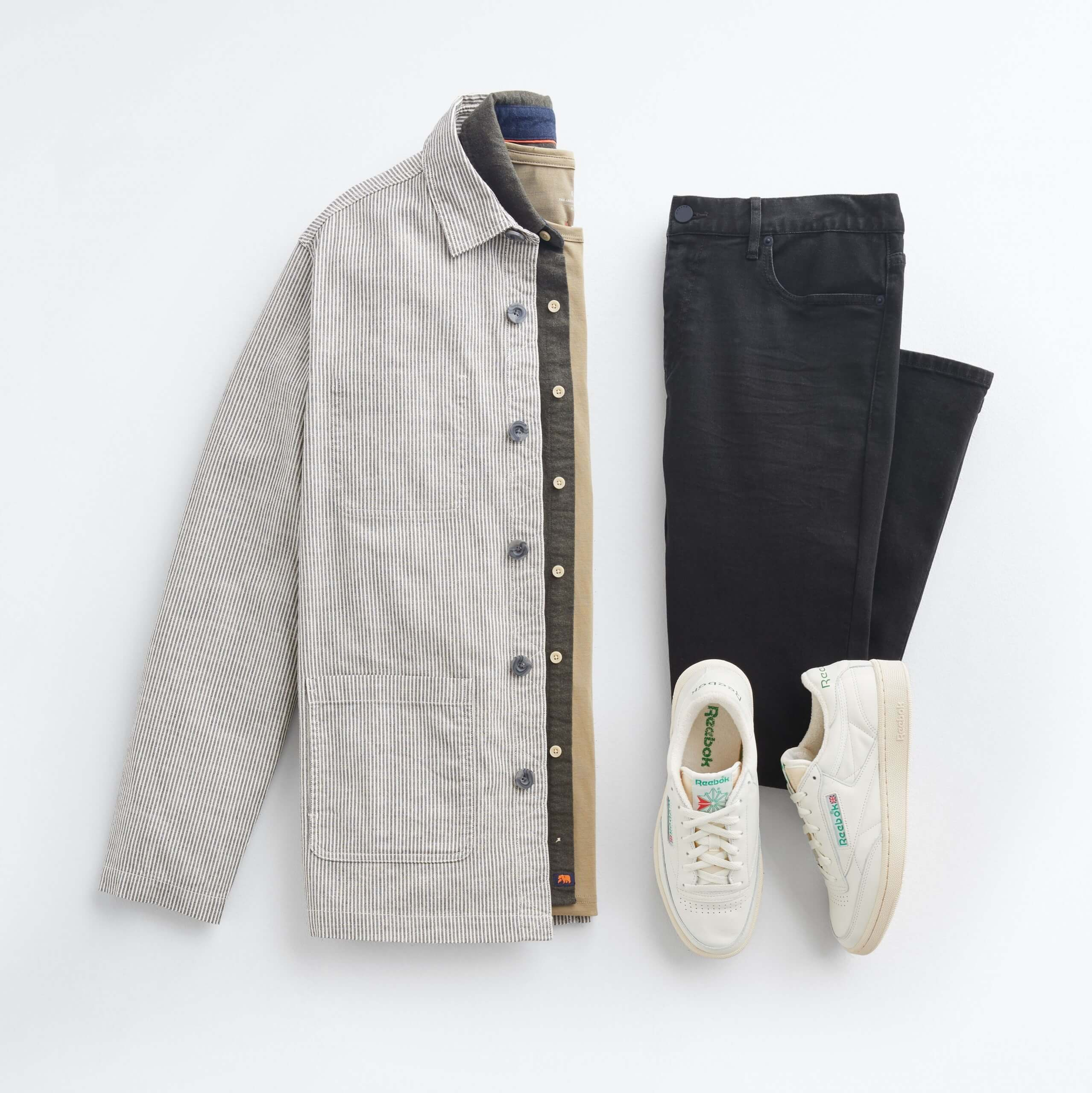 Stitch Fix Men's outfit laydown featuring beige chore jacket over green oxford shirt and olive crewneck t-shirt, next to black jeans and white sneakers.