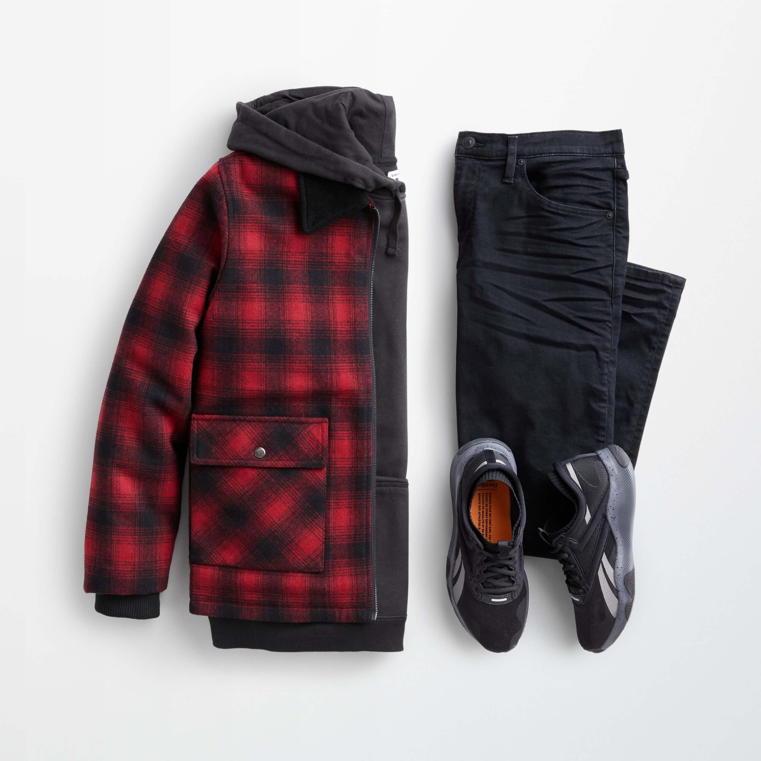 Stitch Fix Men's outfit laydown featuring a red and black plaid trucker jacket over a black hoodie, next to black jeans and black sneakers.