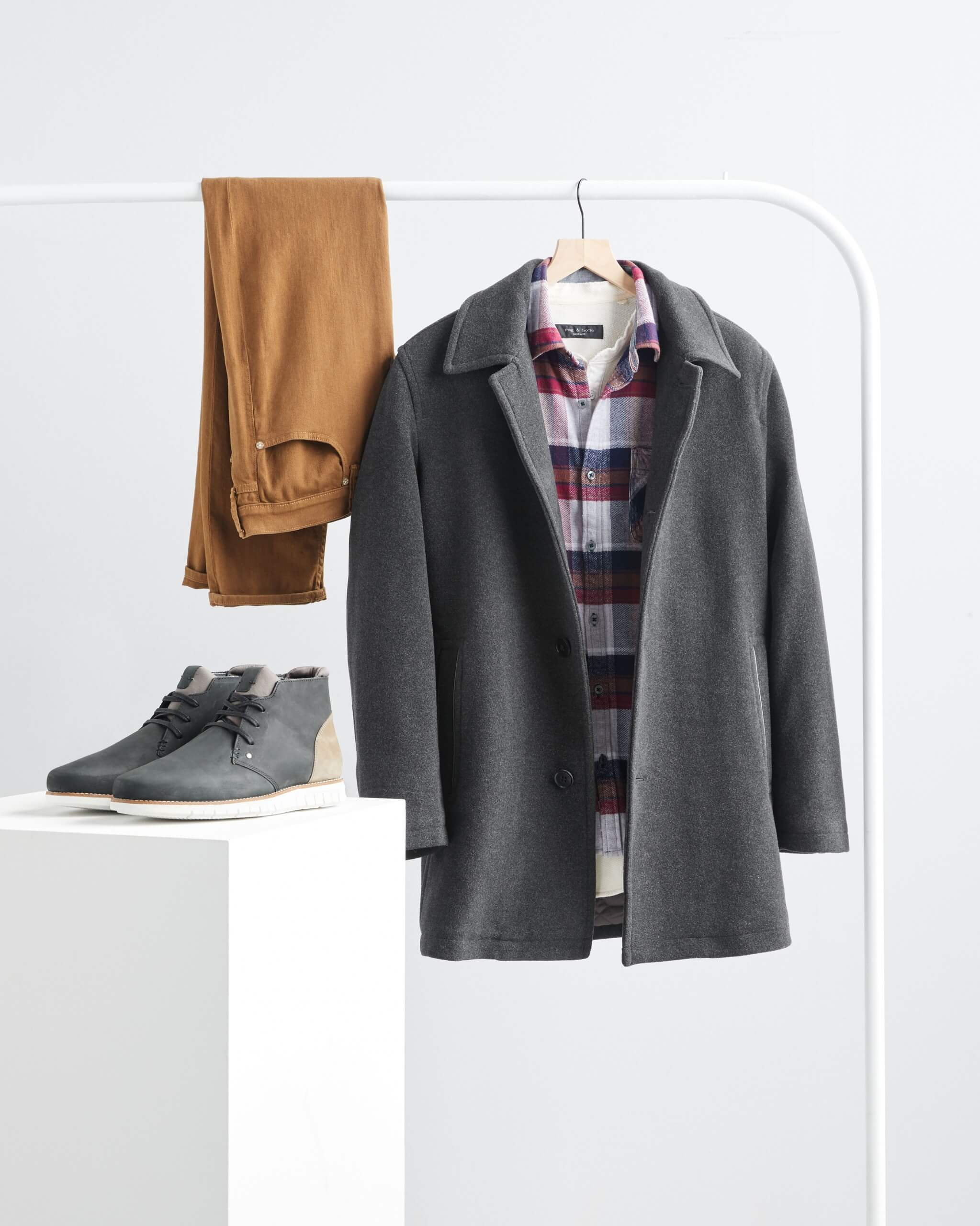 Stitch Fix men's grey wool peacoat, red and blue plaid flannel shirt and brown slim-fit jeans hanging on a rack with grey chukkas on a white podium.
