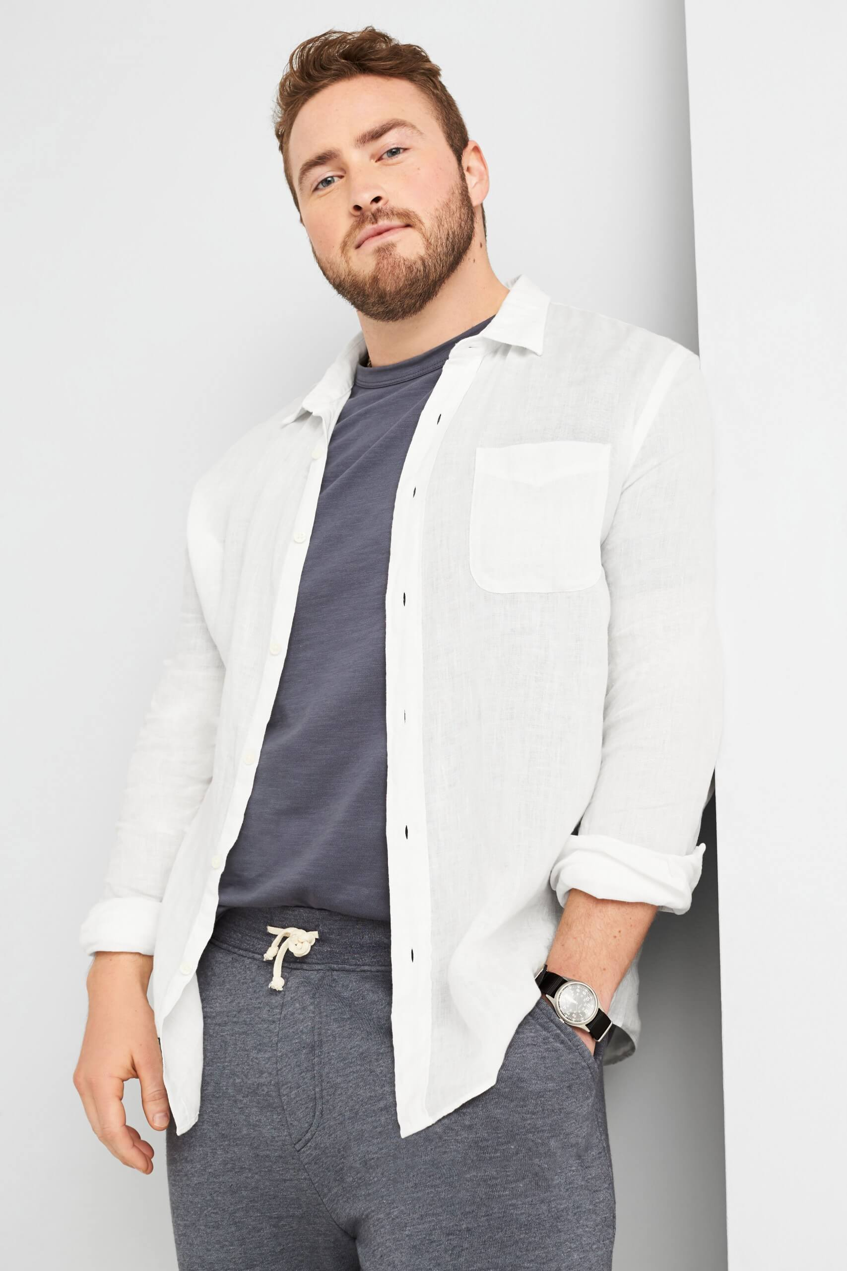 Stitch Fix Men's model wearing white button-down open over grey t-shirt and grey joggers.
