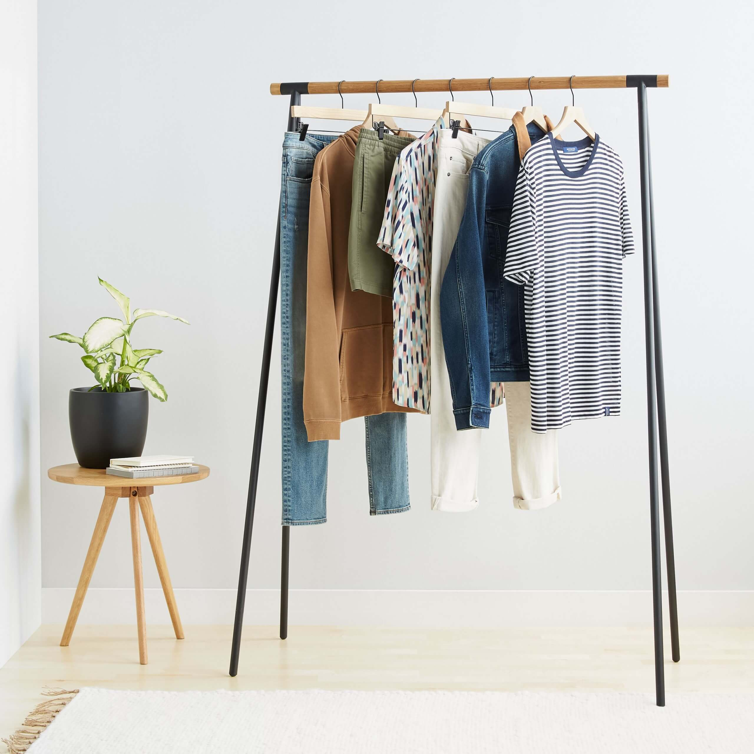 Stitch Fix Men's blue jeans, tan hoodie, olive shorts, printed T-shirt, white pants, denim jacket and blue T-shirt on a rack next to a wooden table with a plant and two books on top and a rug.