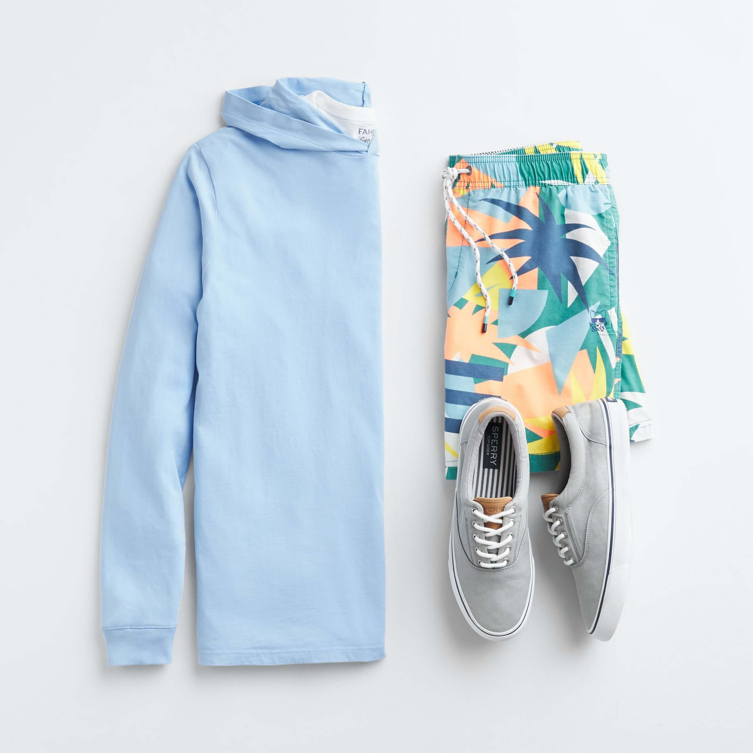 Stitch Fix Men's outfit laydown featuring a blue hoodie, multi-colored tropical board shorts and grey lace-up sneakers.