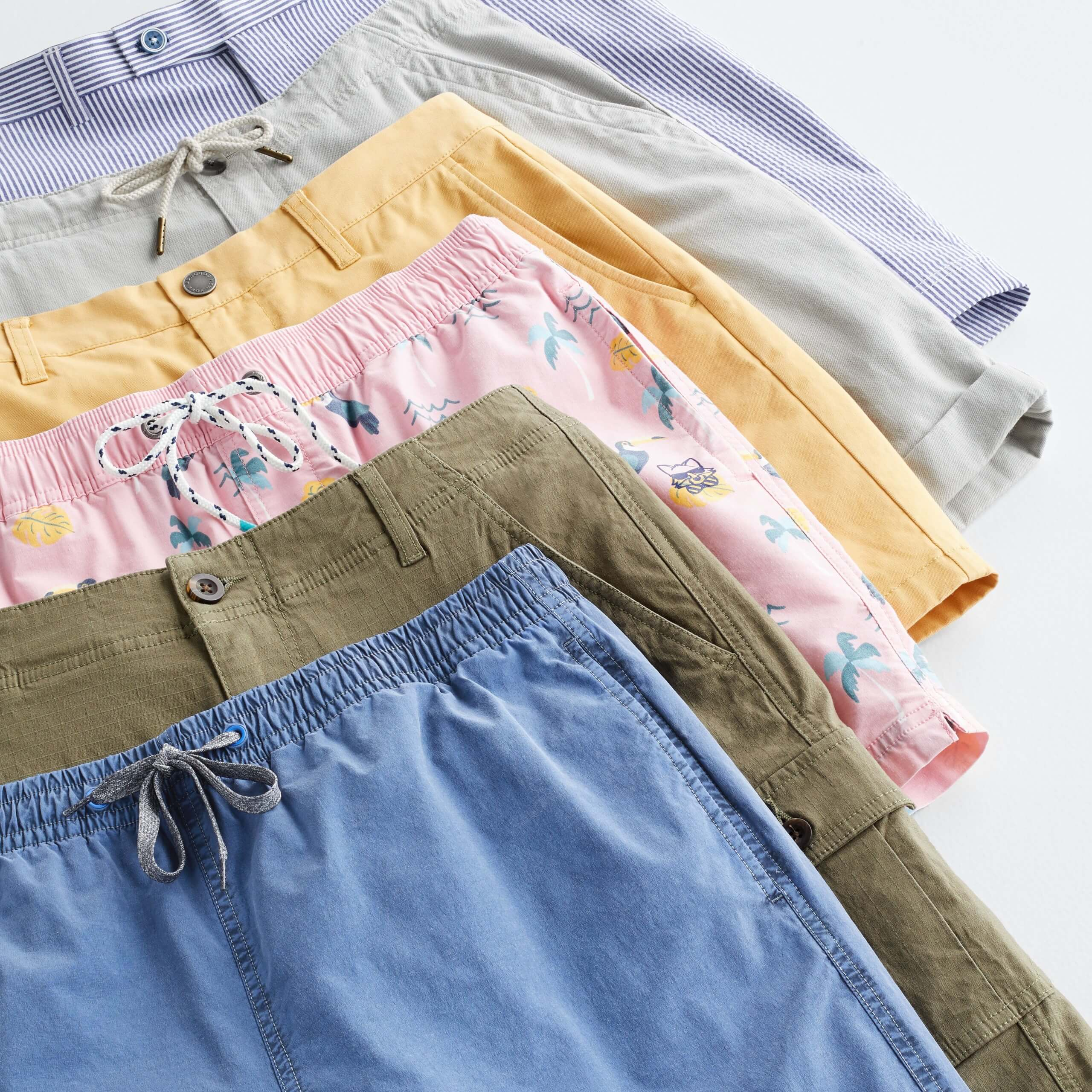 Stitch Fix Men's laydown of stacked shorts in navy, olive, pink, yellow, grey and purple.
