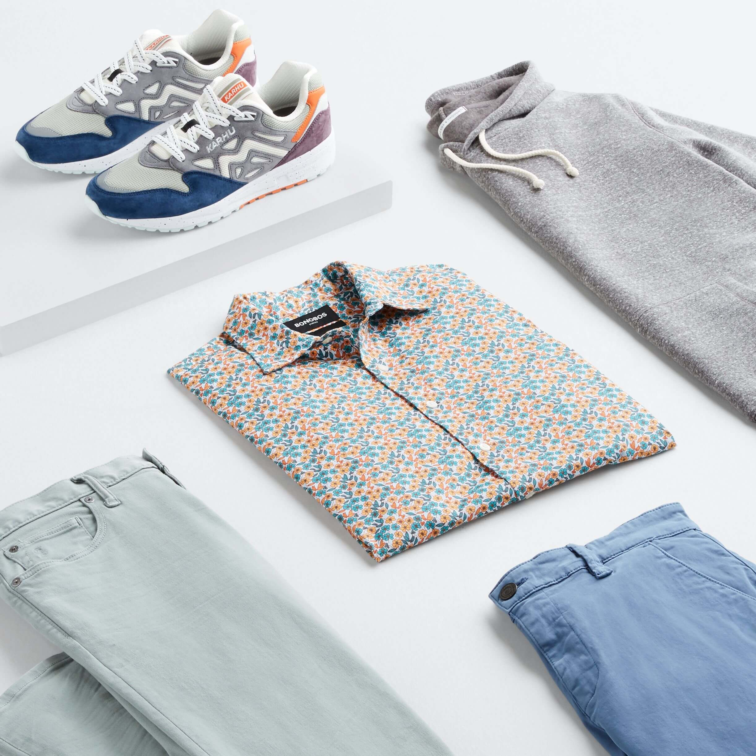 Stitch Fix Men's outfit laydown featuring an orange and blue printed button-up, light-blue pants, grey hoodie, blue shorts and multi-colored sneakers.