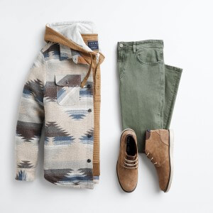 Stitch Fix Men's bohemian outfit laydown with patterned shacket over brown hoodie, green jeans and brown chukkas.