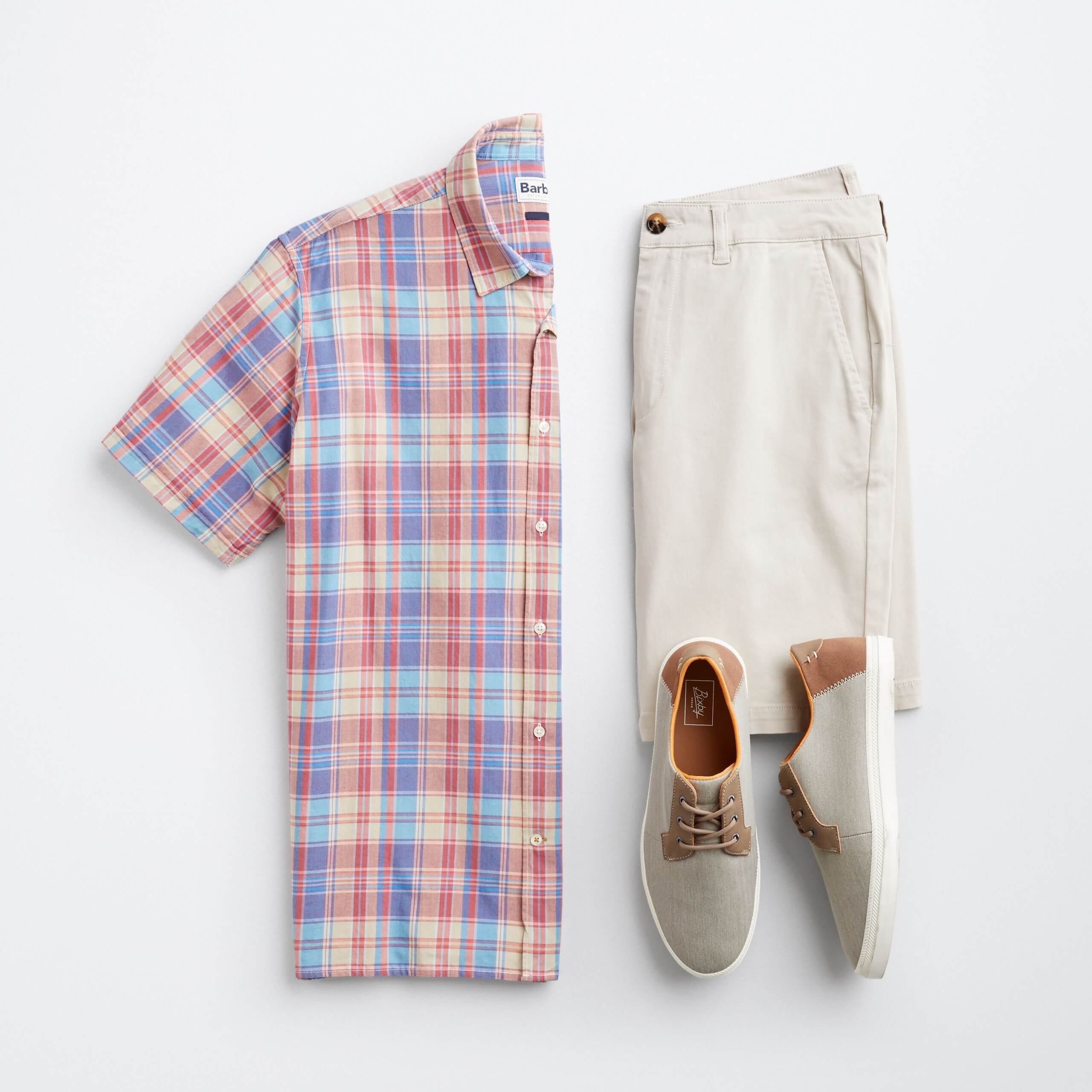 Stitch Fix men's laydown featuring plaid short-sleeved button-down shirt, tan trouser shorts, and grey and brown sneakers.