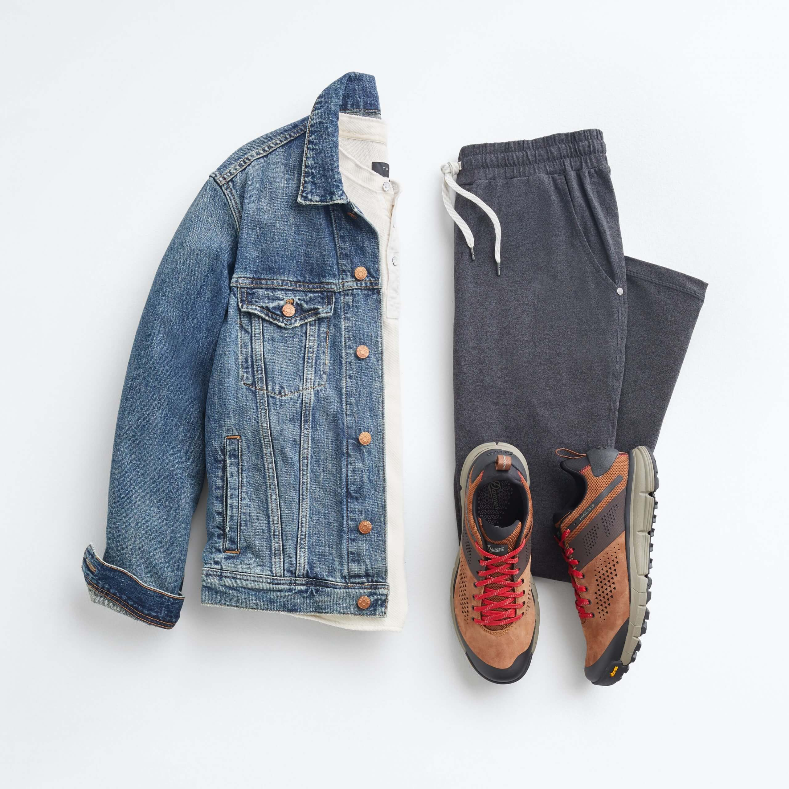 Stitch Fix jean jacket men's outfit laydown with blue jean jacket, light grey henley, navy sweatpants and brown lace-up sneakers with red laces.