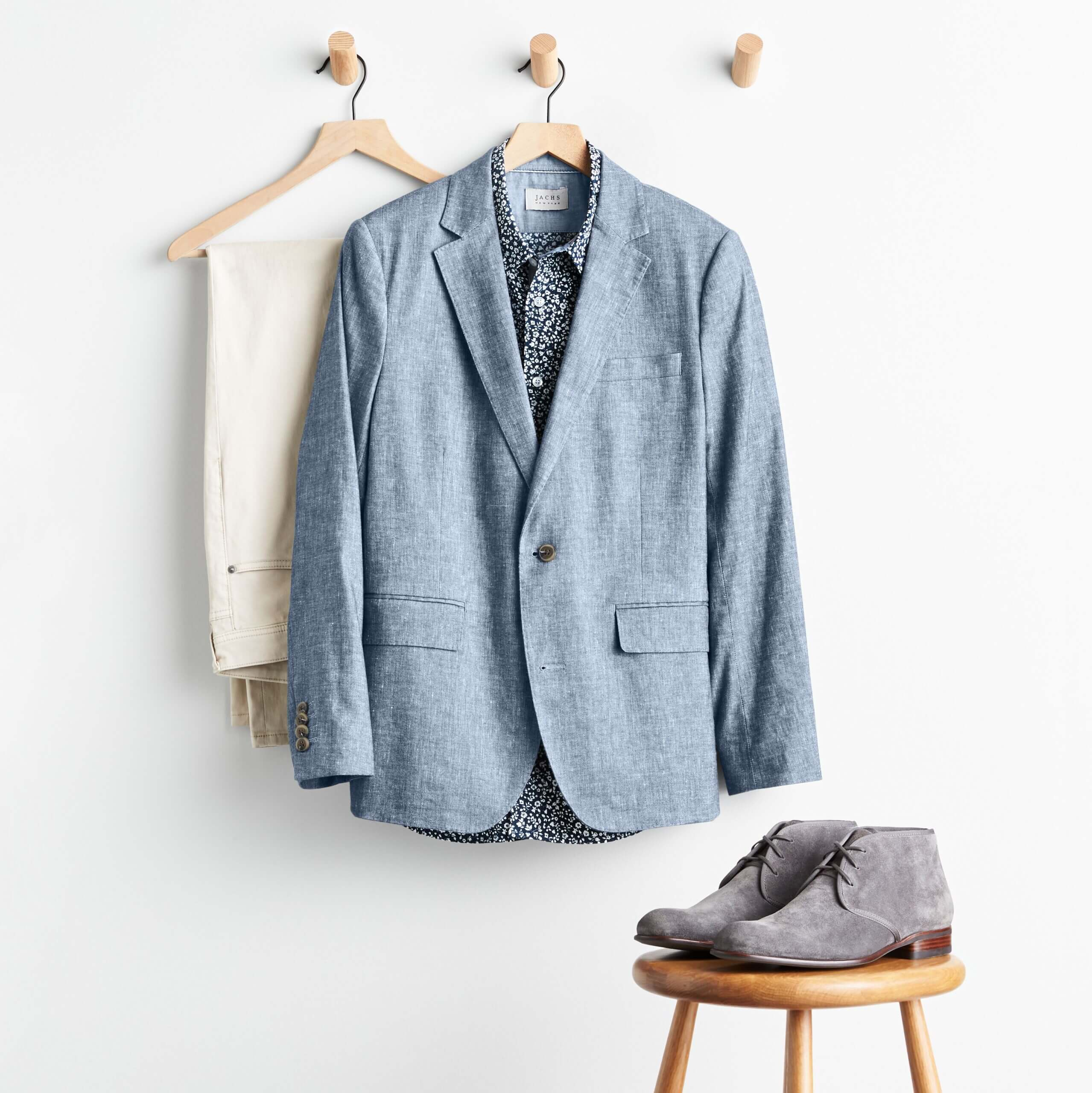 Stitch Fix men's outfit with off-white denim, navy micro-floral button-down shirt and chambray blazer hanging from wall pegs with grey suede chukka boots on stool.