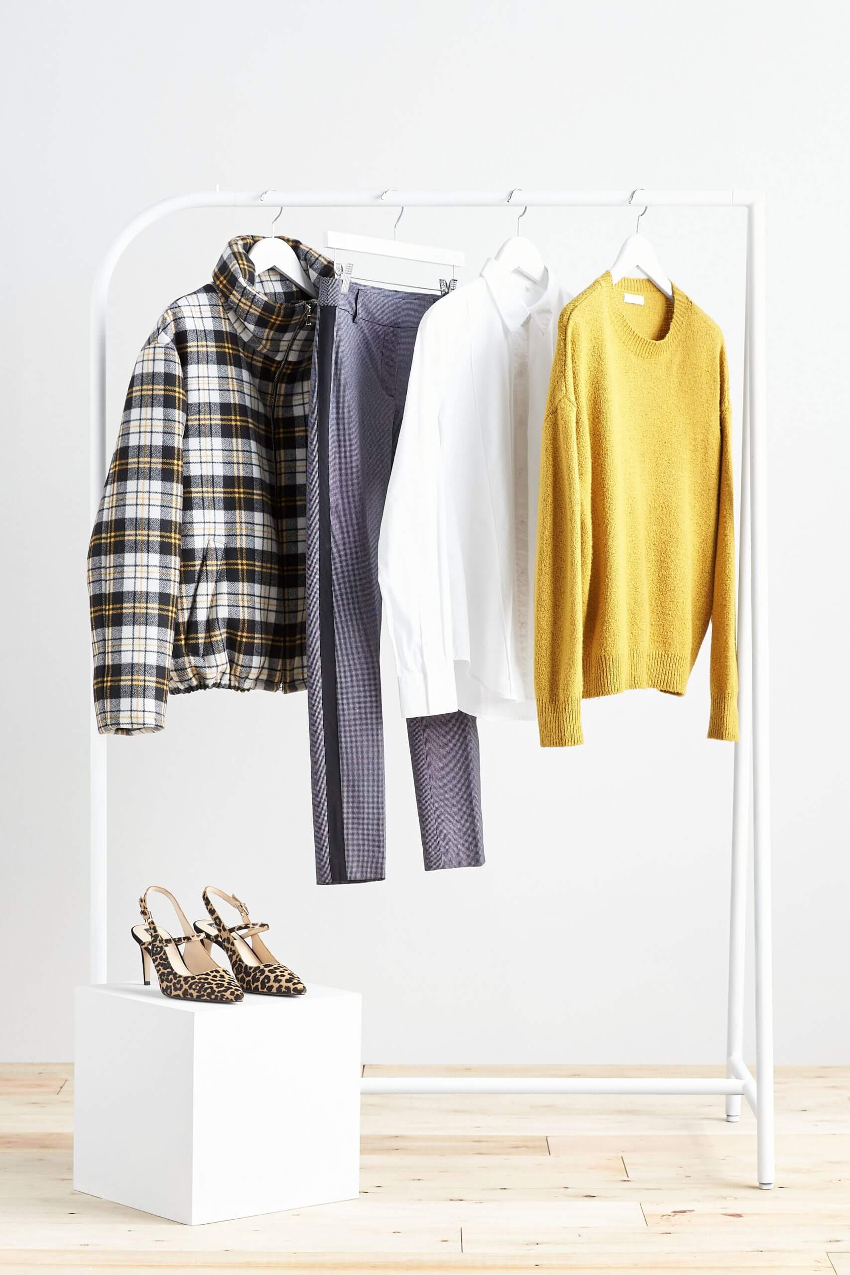 Stitch Fix Women's rack image featuring yellow sweater, white button-down shirt, blue pants and plaid puffer jacket hanging on white rack, next to animal-print heels.