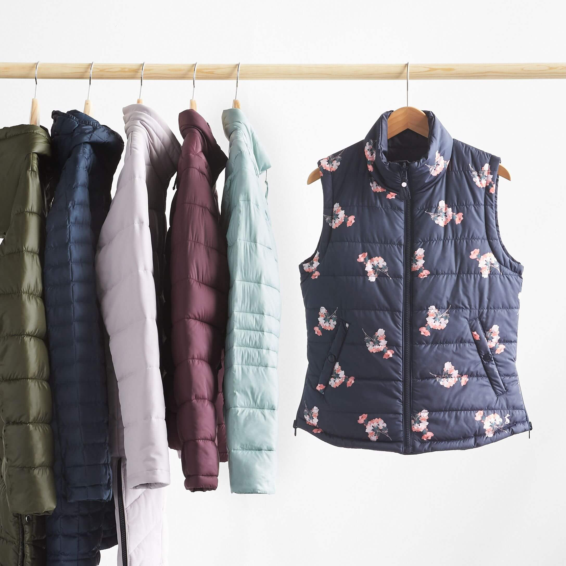 Stitch Fix Women's rack image featuring navy vest with floral print and puffer jackets in light blue, burgundy, lilac, navy and olive green tones hanging on wooden pole.