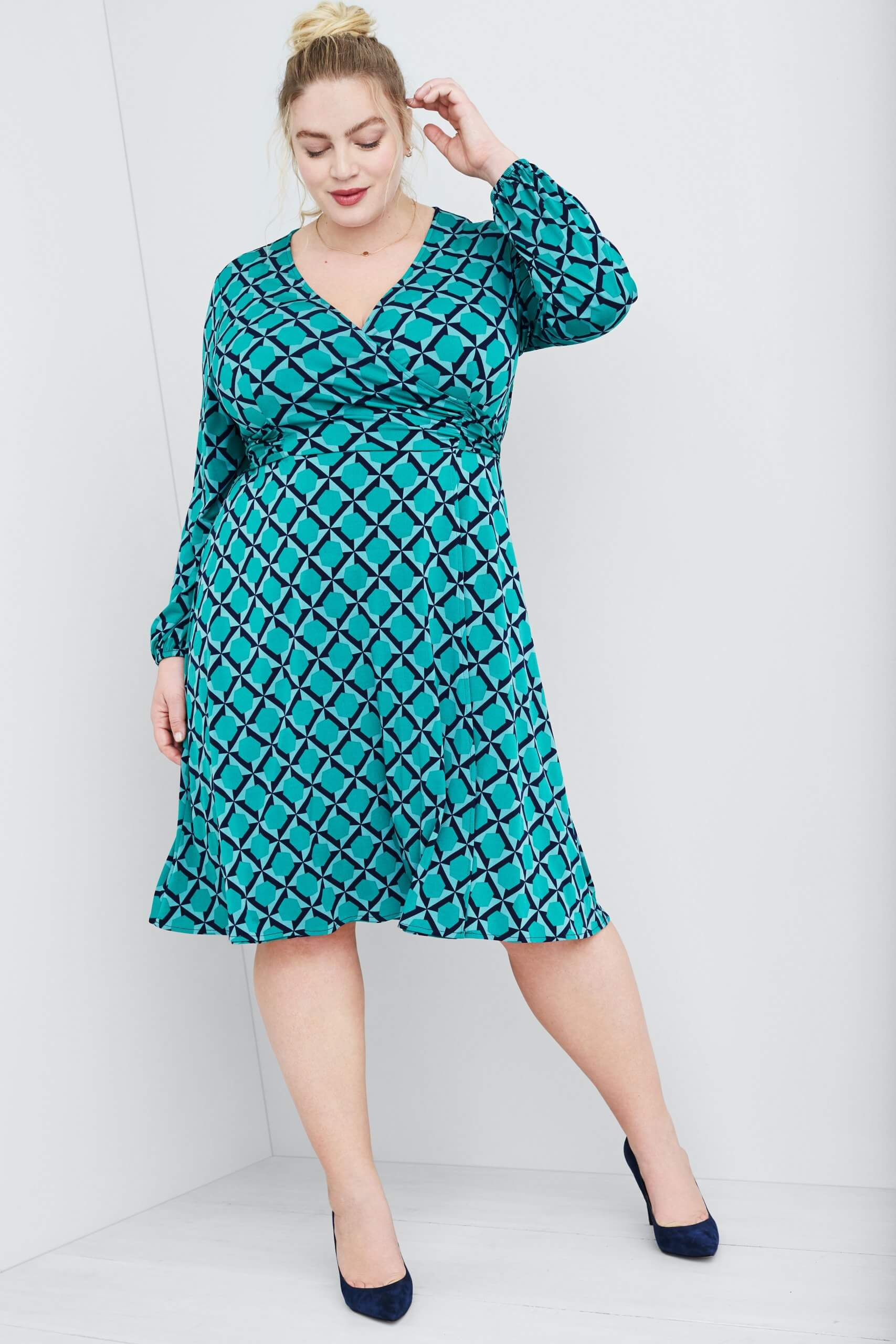 Stitch Fix Women's model wearing teal green abstract print wrap dress and navy heels.