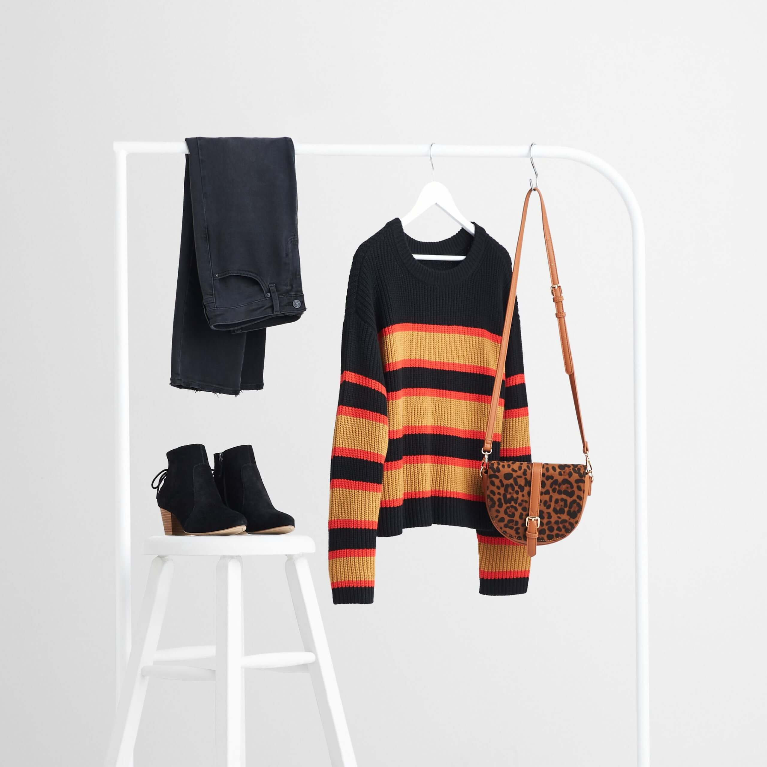 Stitch Fix Women's rack image with brown animal-print purse, black pullover sweater with orange stripes and black jeans on white rack, next to black booties on a white stool.