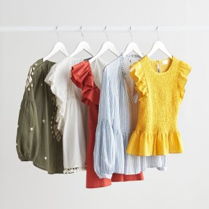 Stitch Fix women's blouse assortment in olive green, white, orange, blue and white stripes and yellow tops with puff sleeves and flutter sleeves hanging on clothing rack.