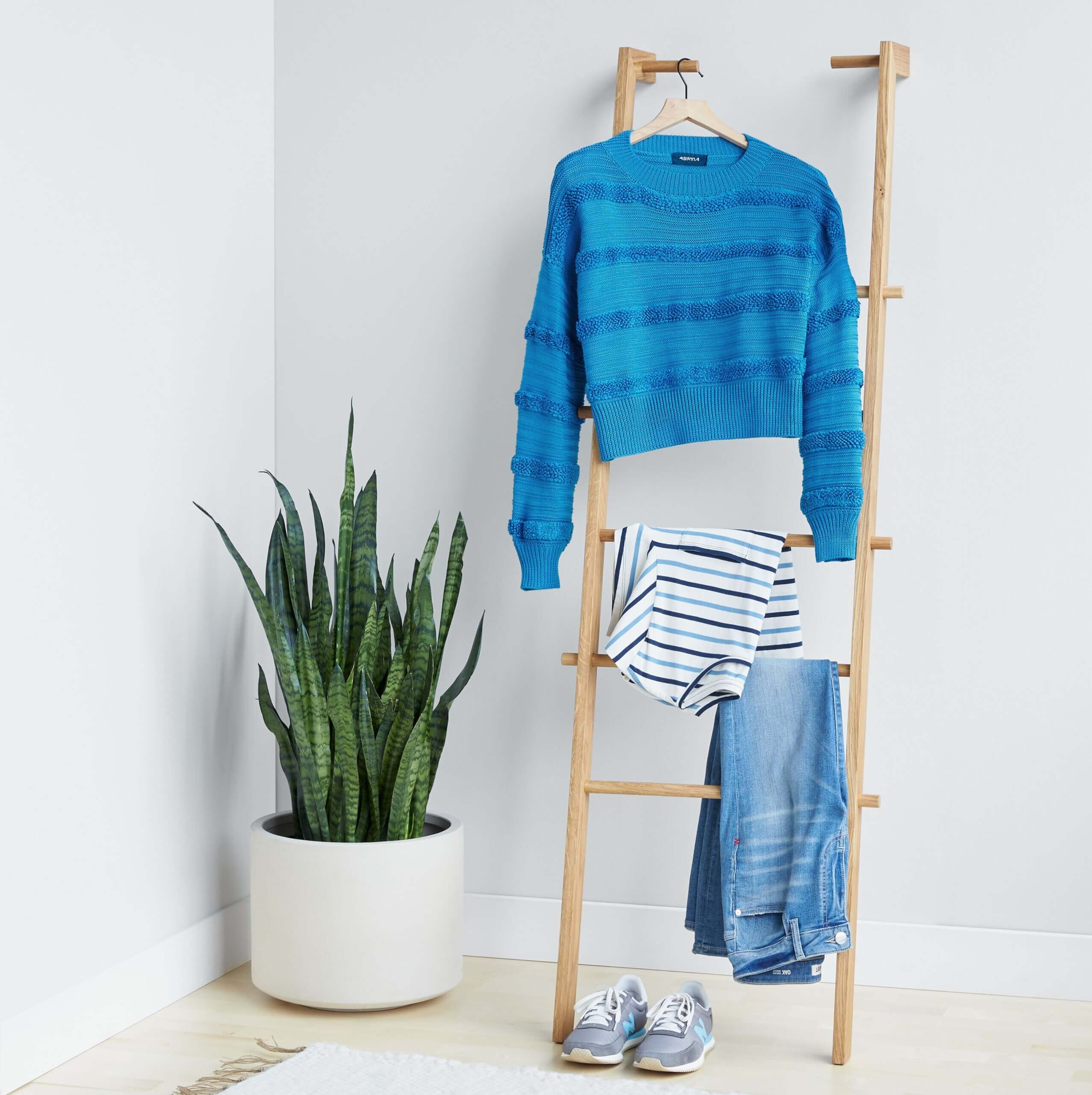 Stitch Fix women's outfit featuring blue textured pullover sweater, white and blue striped shirt and blue jeans hanging on wooden ladder, next to blue sneakers.