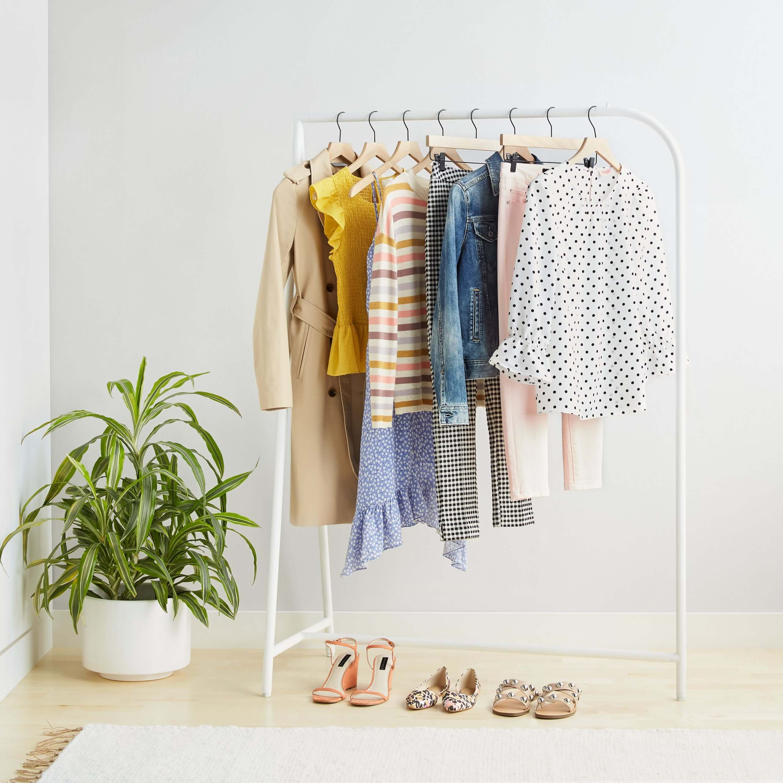 Stitch Fix Women's rack image featuring white polka dot blouse, pink jeans, blue denim jacket, multi-colored striped pullover, yellow blouse and tan trench hanging on white rack with tan slide sandals, animal-print flats and coral wedges on the ground.