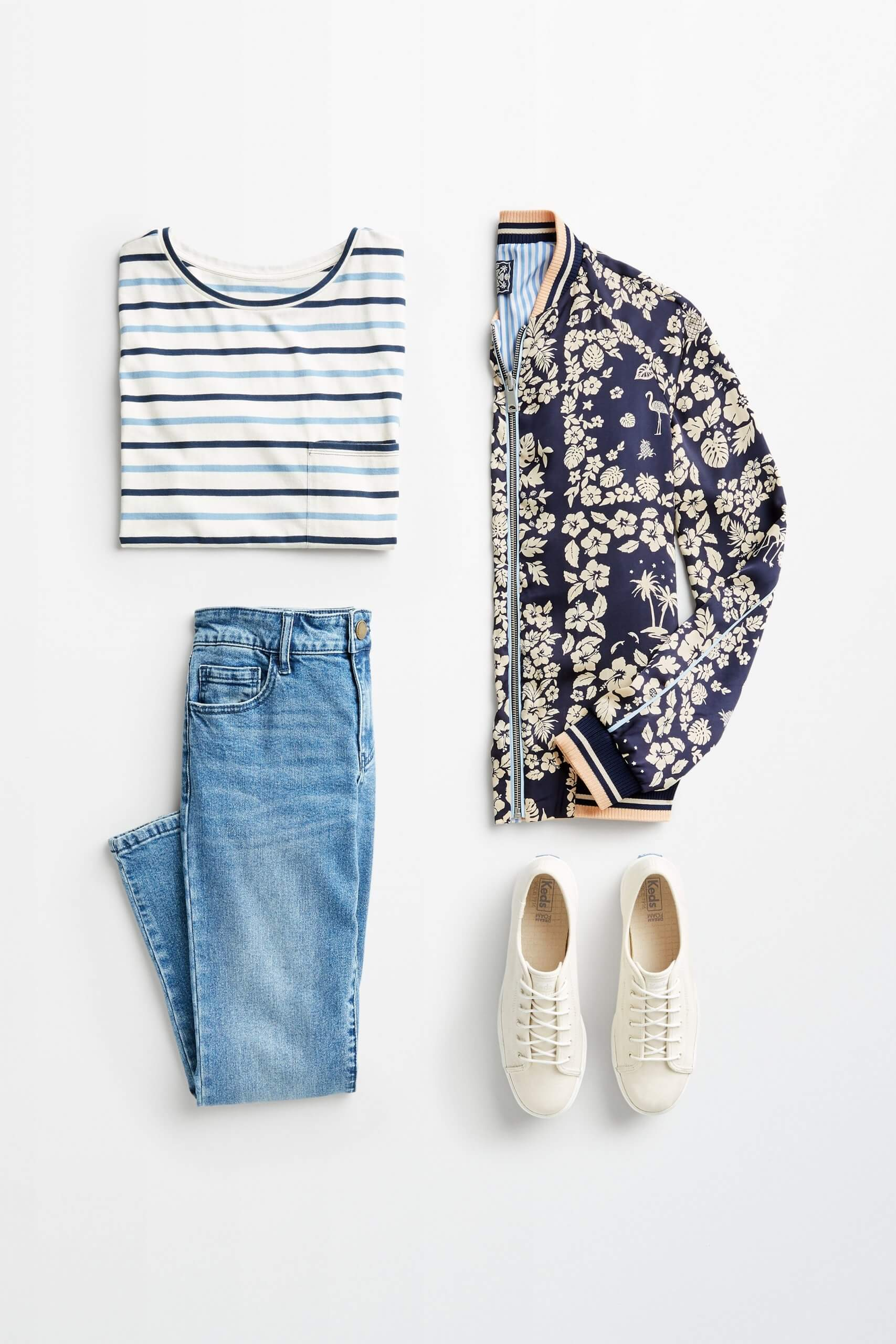 Stitch Fix women's outfit laydown showing how to mix prints and patterns featuring a striped t-shirt, reversible bomber jacket, blue denim and off-white sneakers.