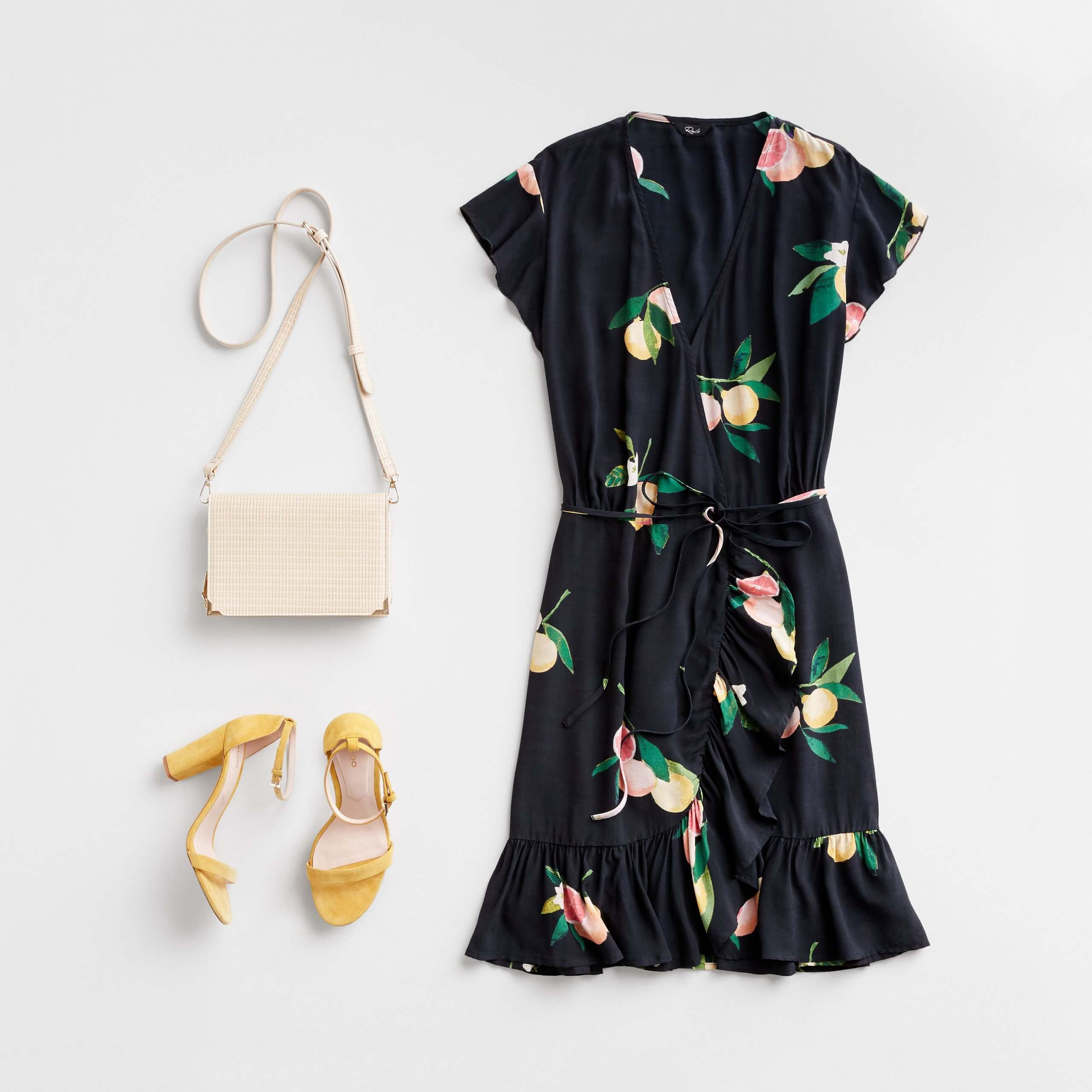 Stitch Fix Women's outfit laydown featuring black lemon-printed wrap dress with yellow block heels and cream crossbody bag.