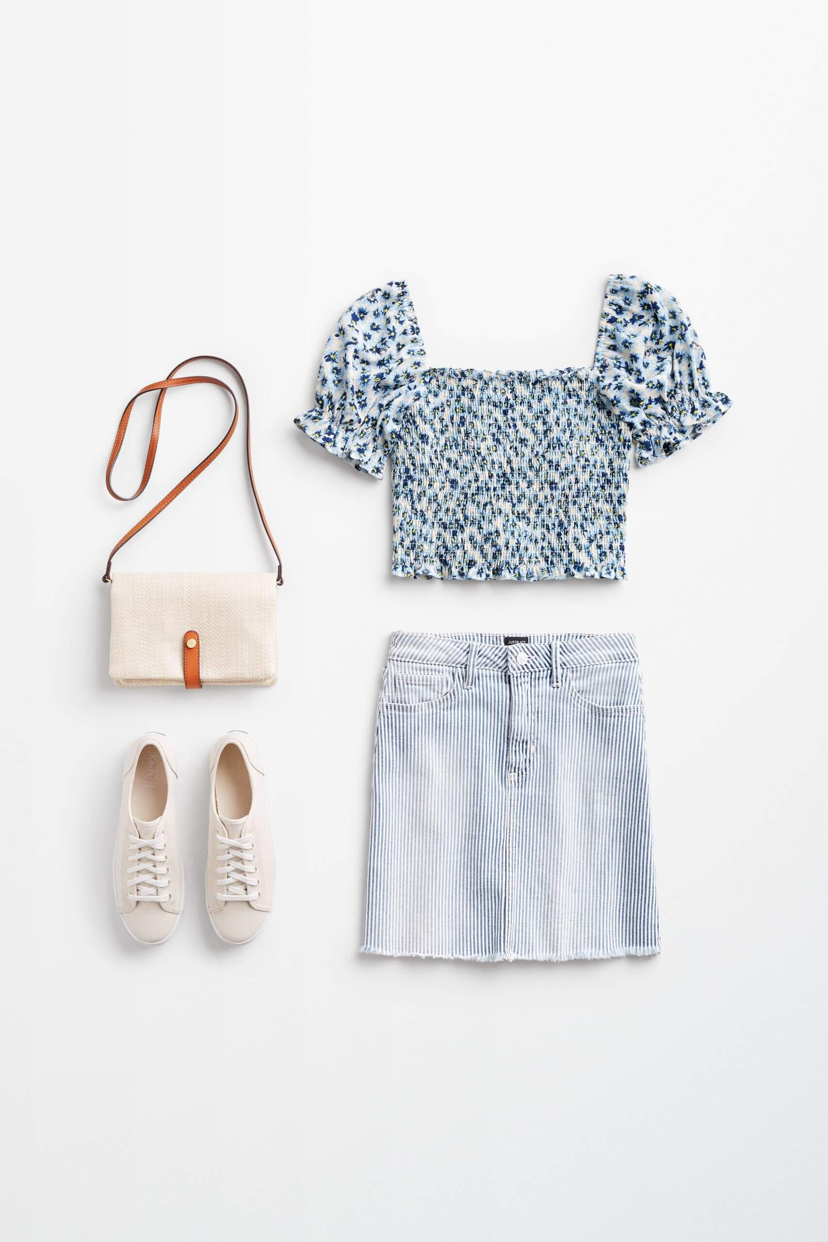 Stitch Fix Women's outfit laydown featuring denim skirt, smocked blouse with puff sleeves, sneakers and crossbody bag.