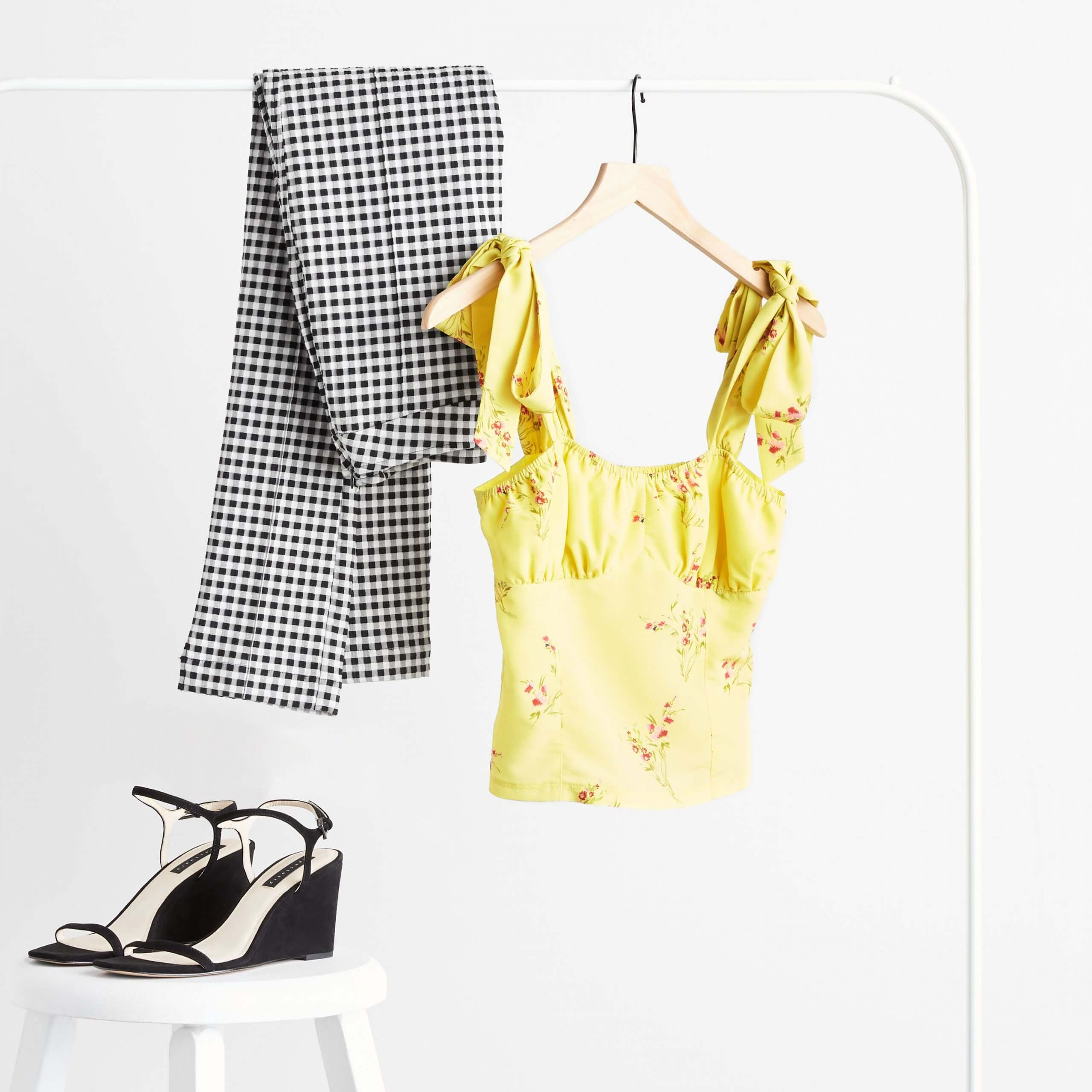 Stitch Fix Women's yellow floral ruffle sleeve top and black and white checkered pants hanging on rack next to black wedges on white stool.