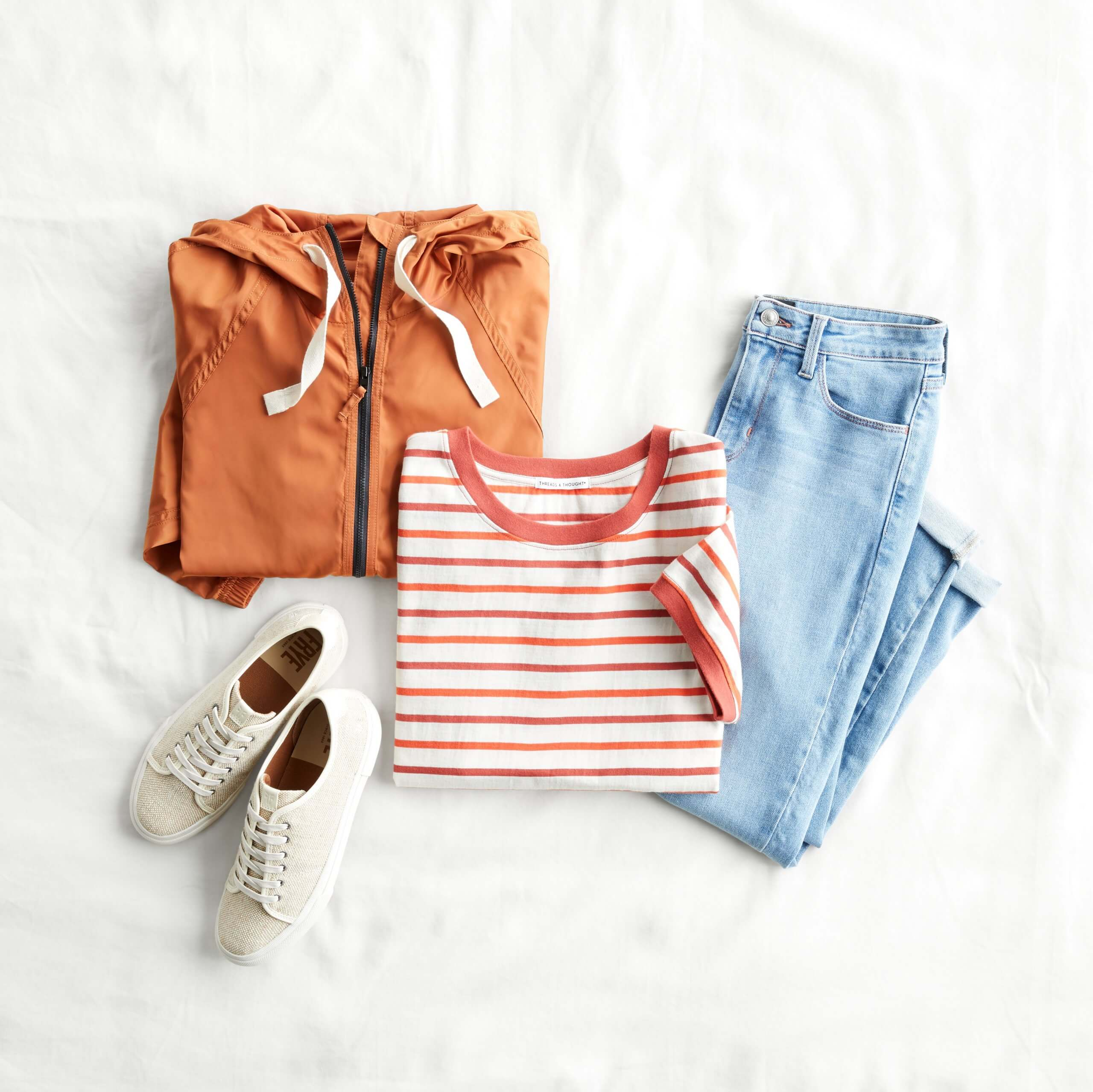 Stitch Fix Women's outfit laydown featuring orange and white striped tee, lightwash jeans, white sneakers and orange rain jacket.