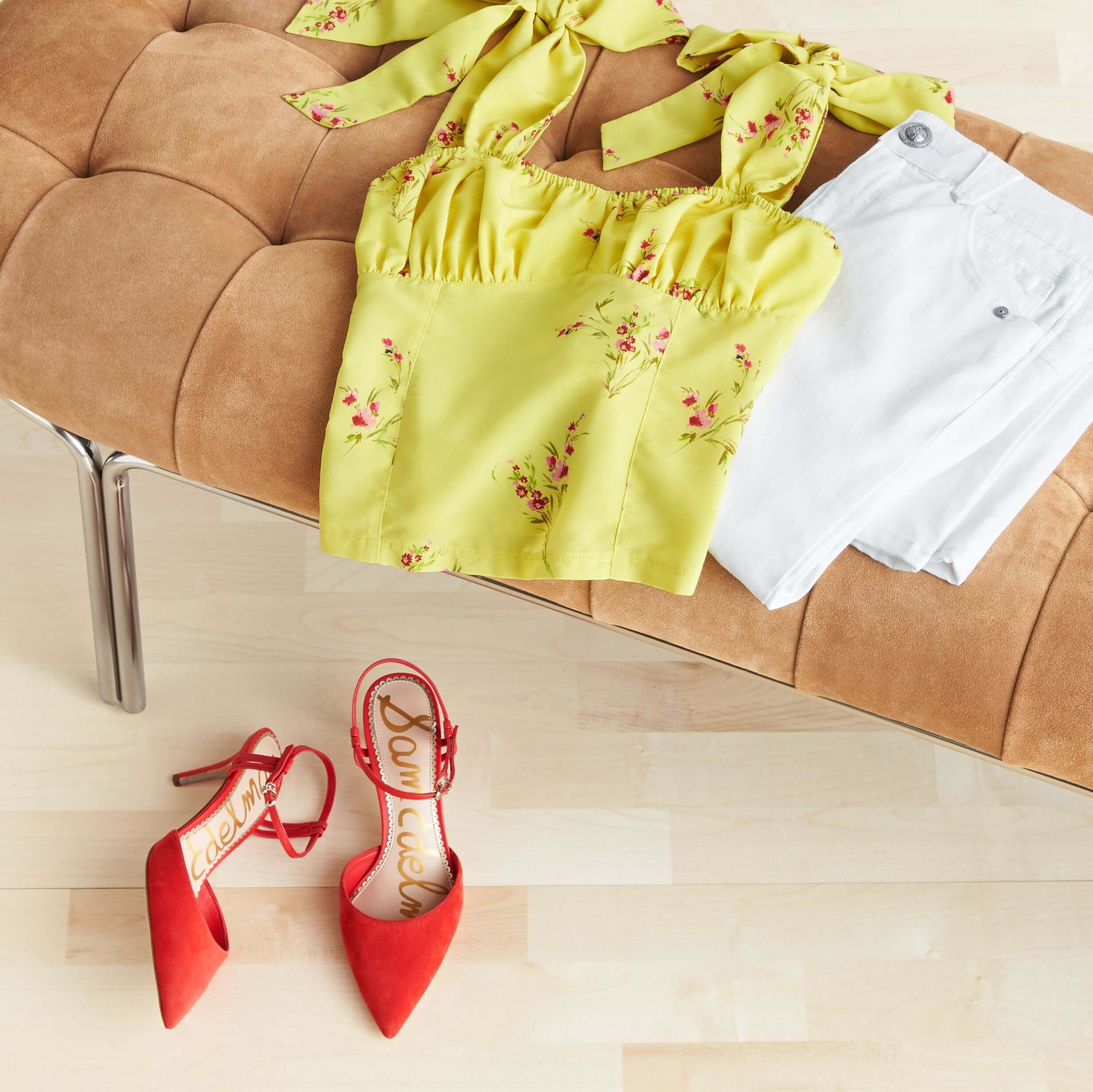 Stitch Fix Women's outfit laydown featuring yellow floral tie-sleeve tank and white denim on tan bench, next to red pointed heels on the floor.