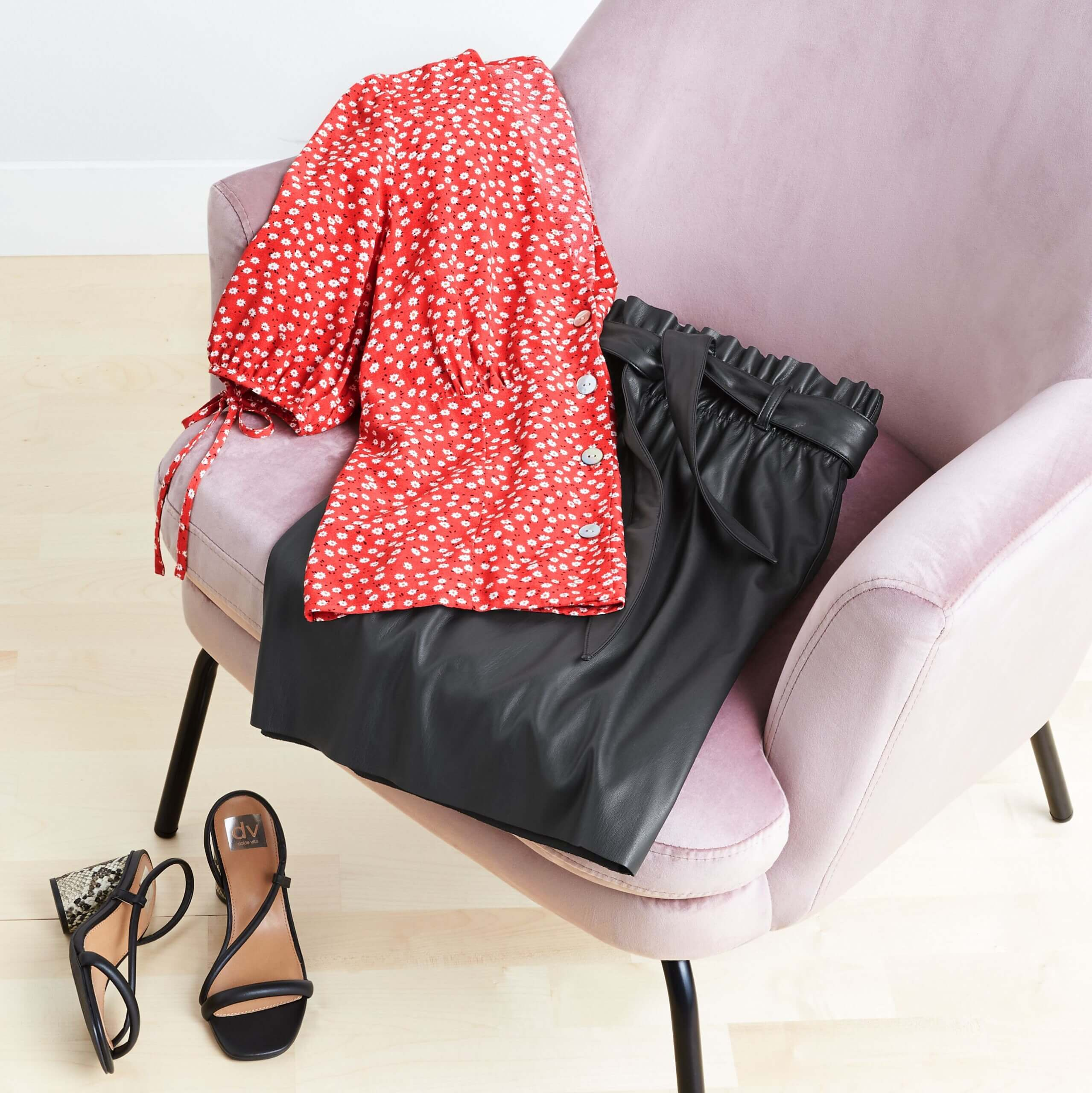 Stitch Fix Women's outfit laydown featuring red top with dainty white florals, black leather skirts on blush pink chair next to black wedges on the floor.