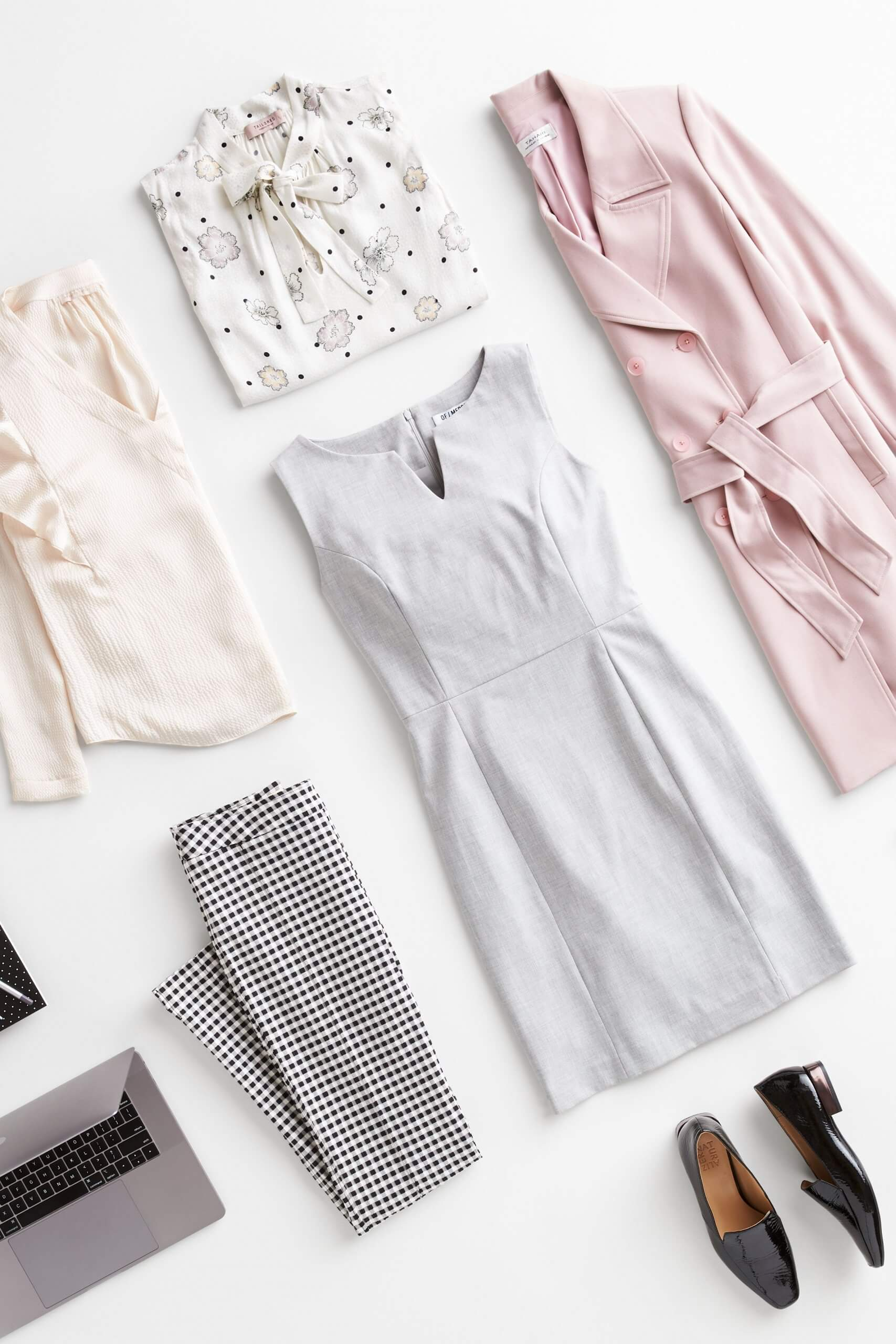 Stitch Fix Women's outfit laydown featuring pink trench jacket, white patterned tie-neck blouse, cream blouse, black and white checkered pants, grey sheath dress and black loafers.