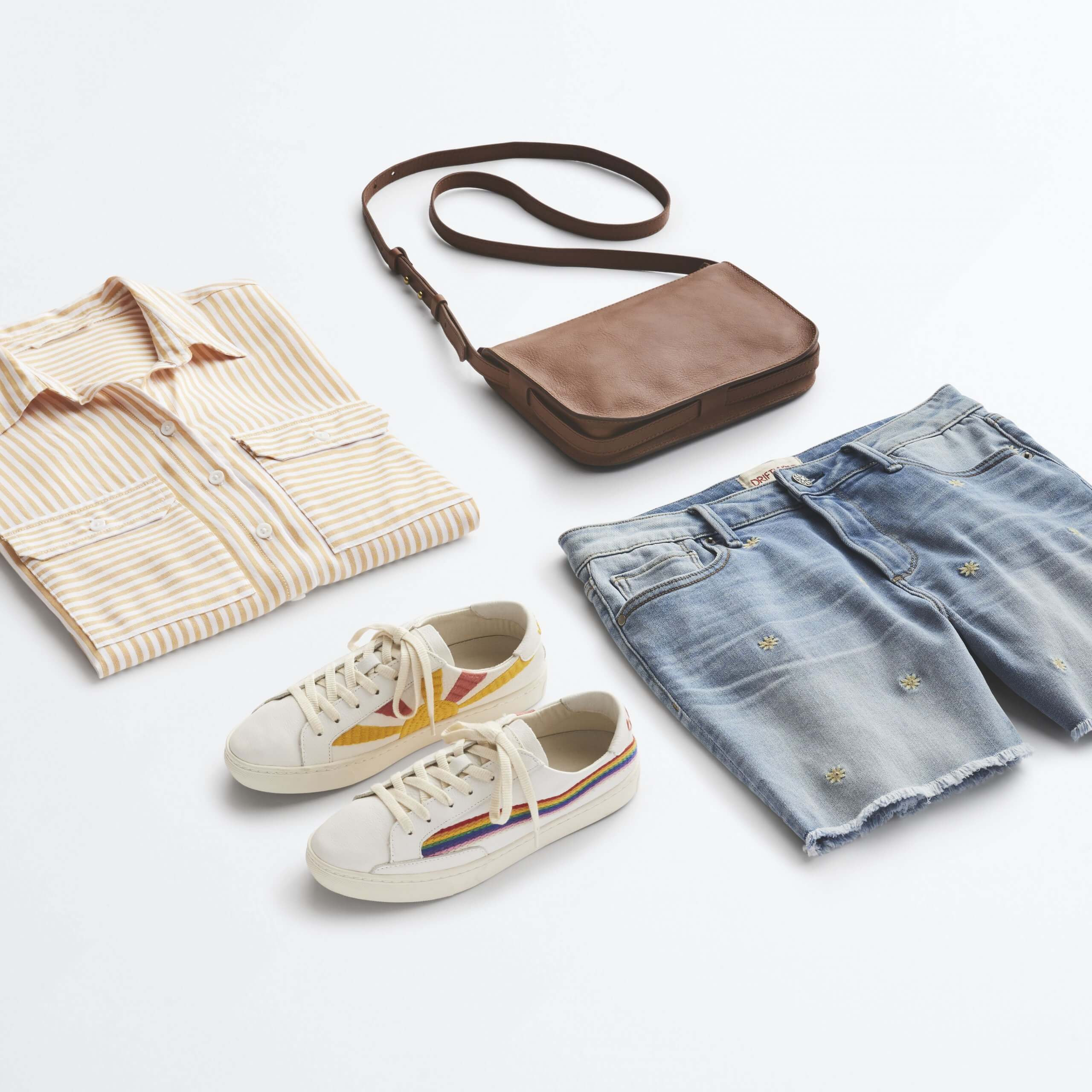 Stitch Fix Women's outfit laydown featuring cream striped button-down shirt, cut-off denim shorts, white sneakers with rainbow stripe and brown crossbody bag.