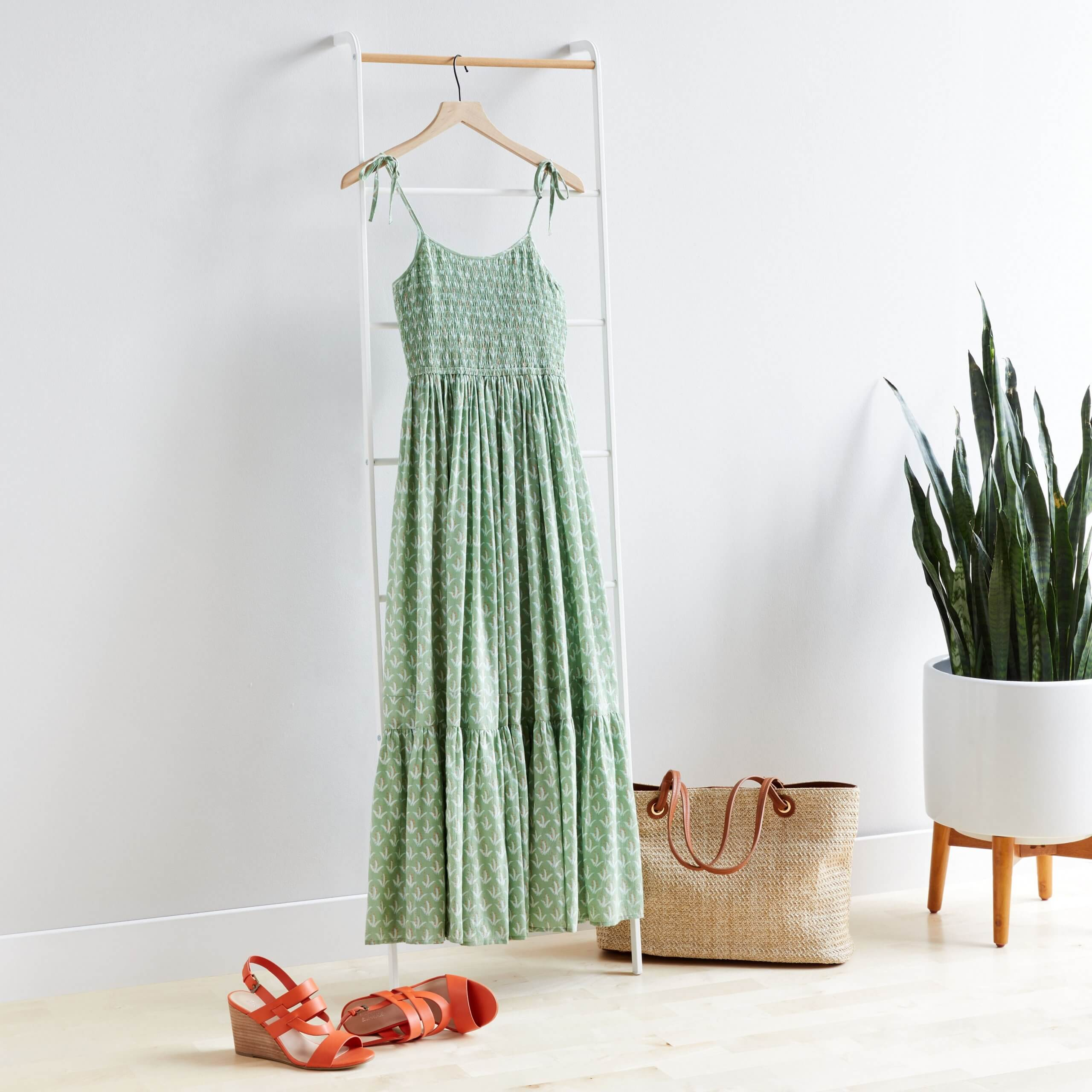 Stitch Fix Women's green maxi dress hanging on white rack next to tan tote bag and orange wedges.