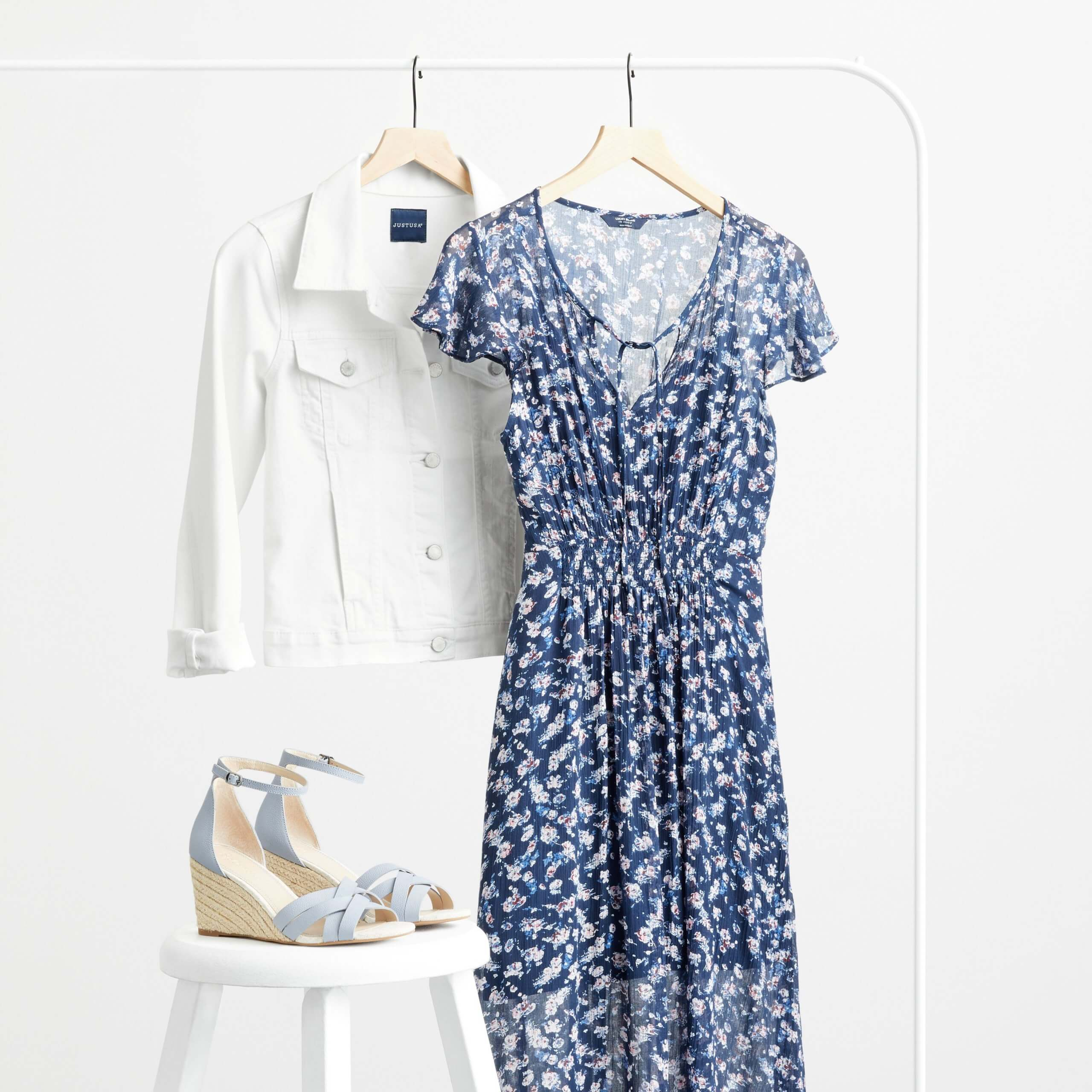 Stitch Fix Women's rack image featuring white denim jacket and blue and white printed midi dress on hangers on white rack, next to blue wedges on a white stool.