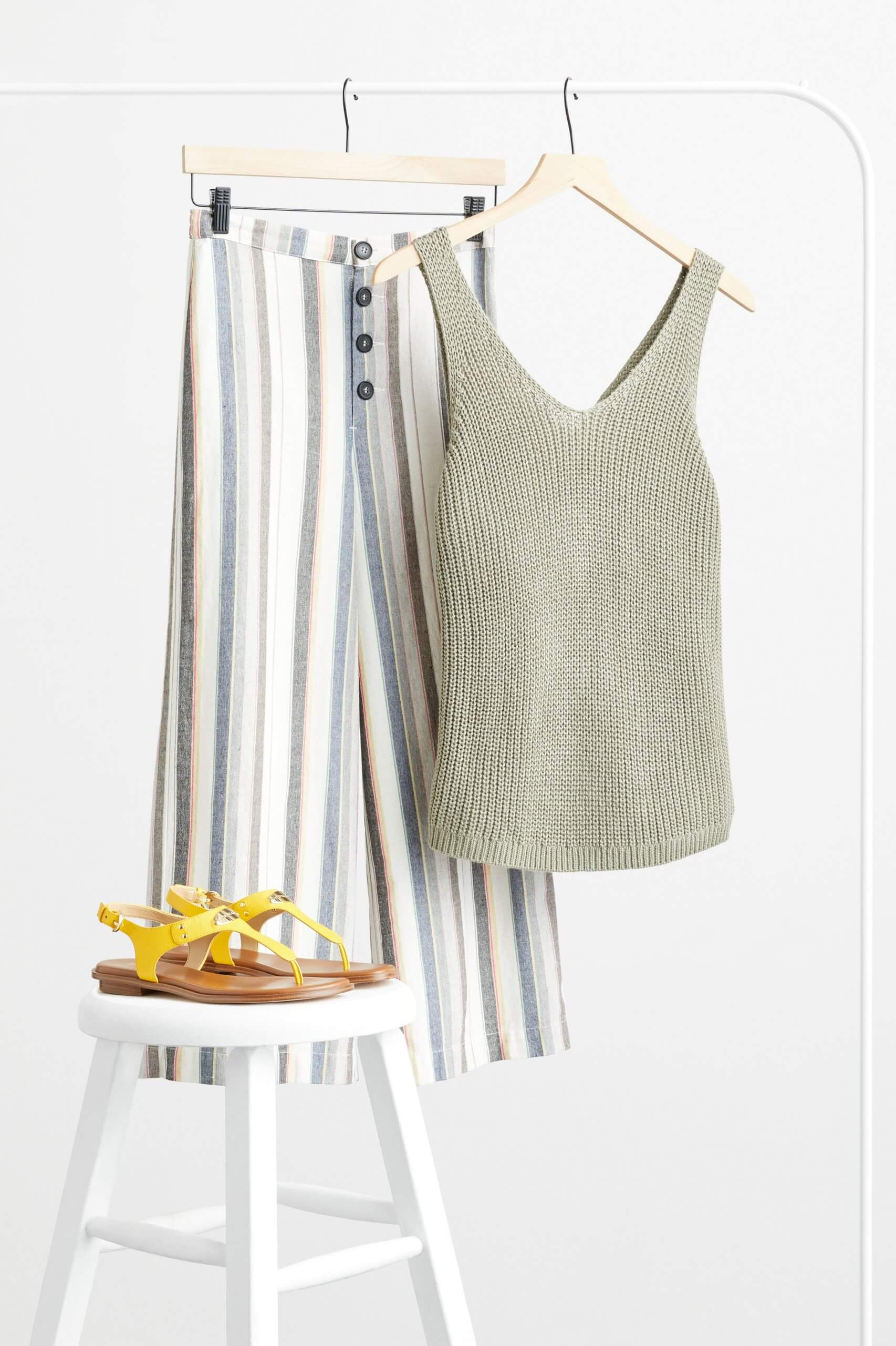 Stitch Fix Women's olive v-neck sweater tank and striped wide-leg pants hanging on white rack next to  yellow sandals on a white stool.