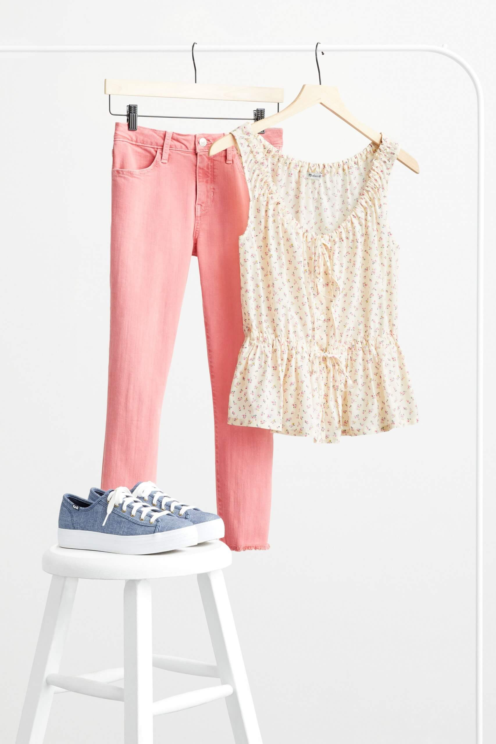 Stitch Fix Women's pink skinny jeans and yellow-patterned blouse hanging from a rack behind blue sneakers on stool.