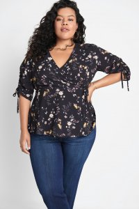 Stitch Fix model wearing plus-size clothing featuring black floral wrap blouse with tie-sleeve details and blue jeans.
