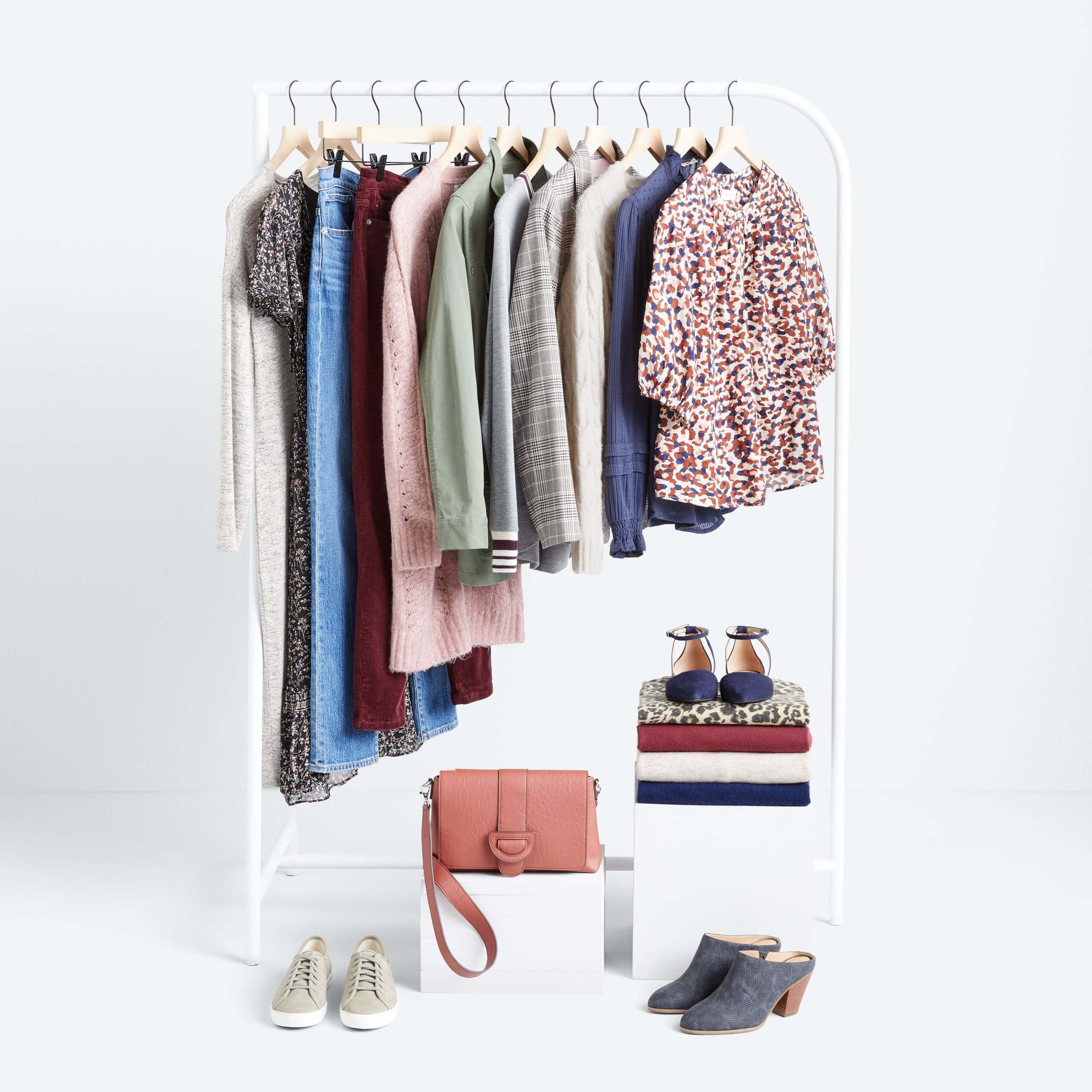 Stitch Fix Women's rack image featuring red, wnite and blue printed blouse, navy blouse, cream pullover, plaid blazer, grey pullover, green jacket, pink cardigan, burgundy jeans, blue jeans and black printed dress hanging on white rack with tan sneakers and navy mules on the floor, next to pink bag and folded shirts in navy, tan and burgundy,  with animal-print flats on white block.