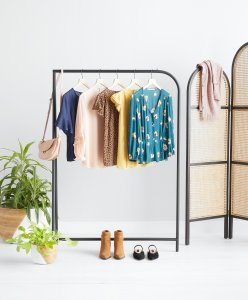 Stitch Fix women's beige purse on a rack with five tops in an assortment of colors and patterns next to two potted plants, boots and a pair of flats. A room divider with a blush cardigan slung over it.