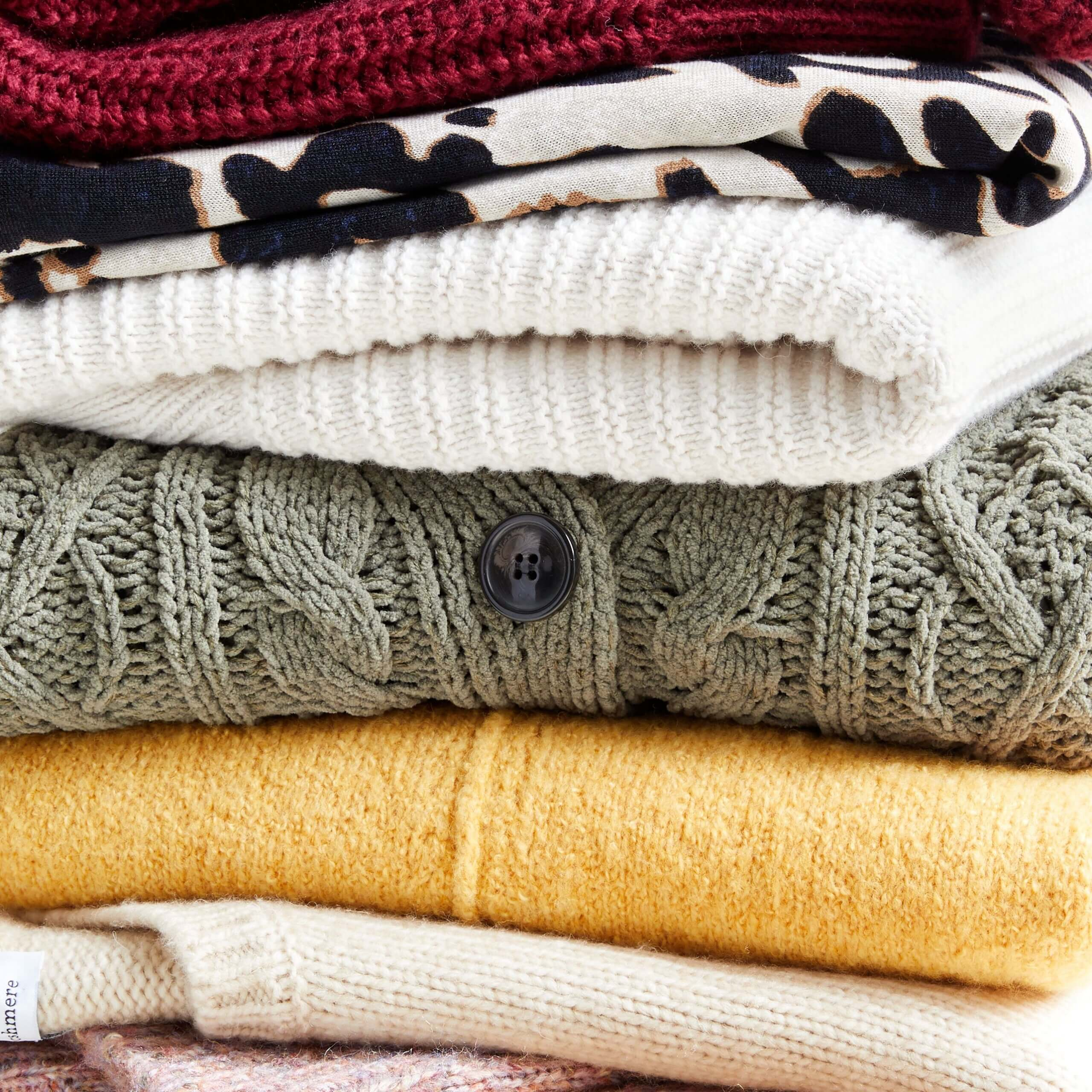 Stitch Fix Women's stack of sweaters in burgundy, beige and brown animal print, cream olive green, yellow and beige.